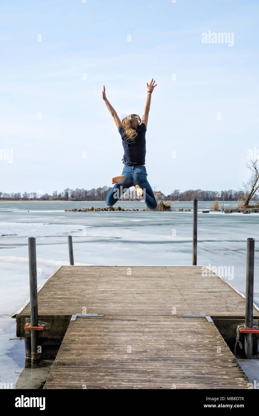 Joven saltando por el agua con muelle de felicidad Imagen De Stock
