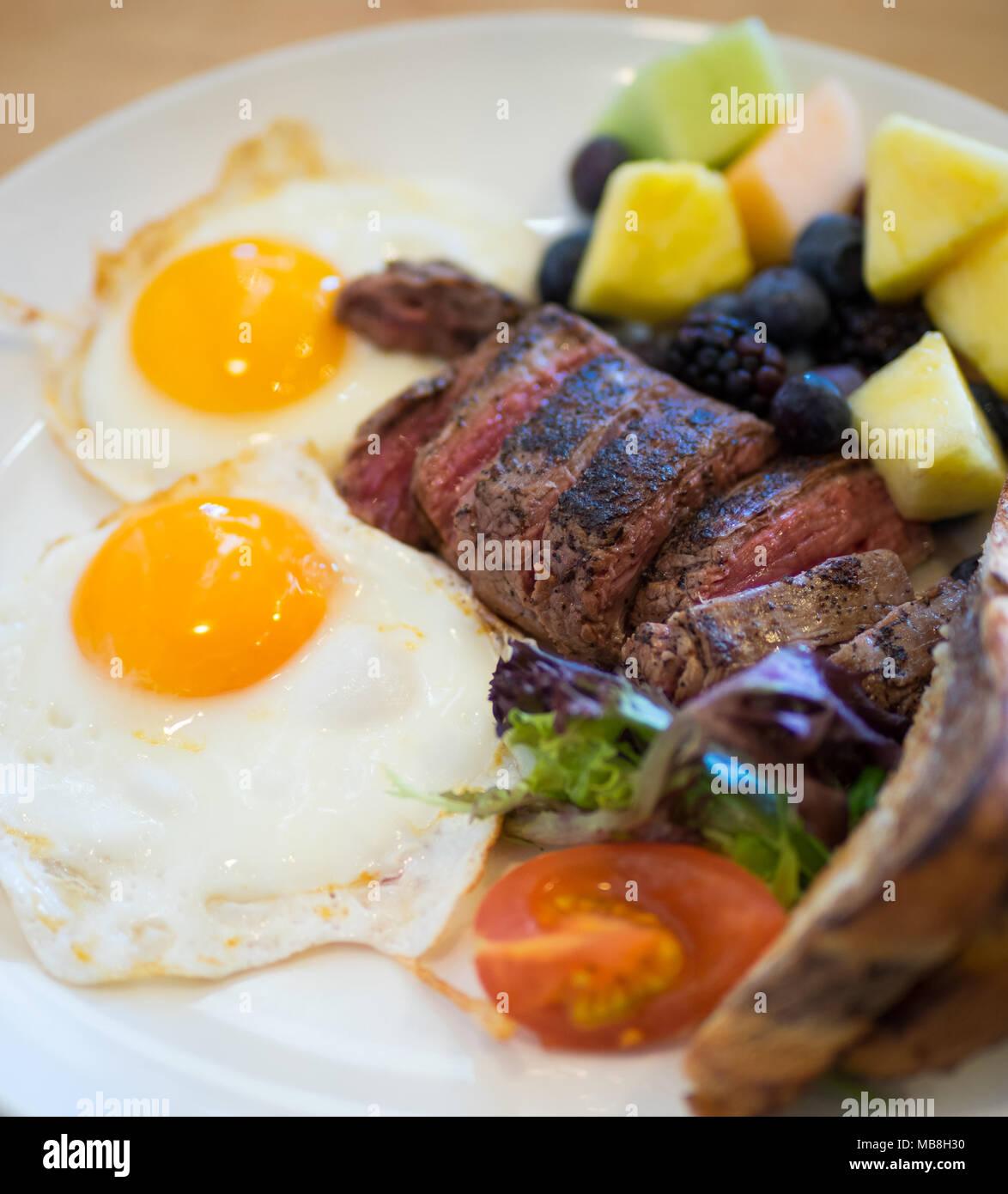 Steak huevos para desayunar en Natal Diner en Saskatoon, Canadá. Medio raro el flanco bistec, Sunny side up huevos, mármol centeno tostadas, fruta y foto. Imagen De Stock
