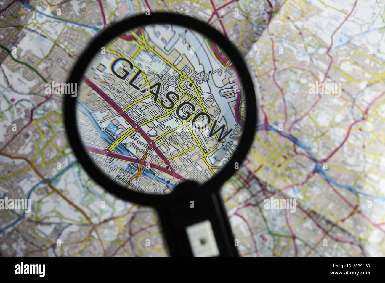 Una ordenanza encuesta mapa de Glasgow y la rodea con una lupa rescatando y resaltando la palabra Glasgow impresas en el mapa. Imagen De Stock