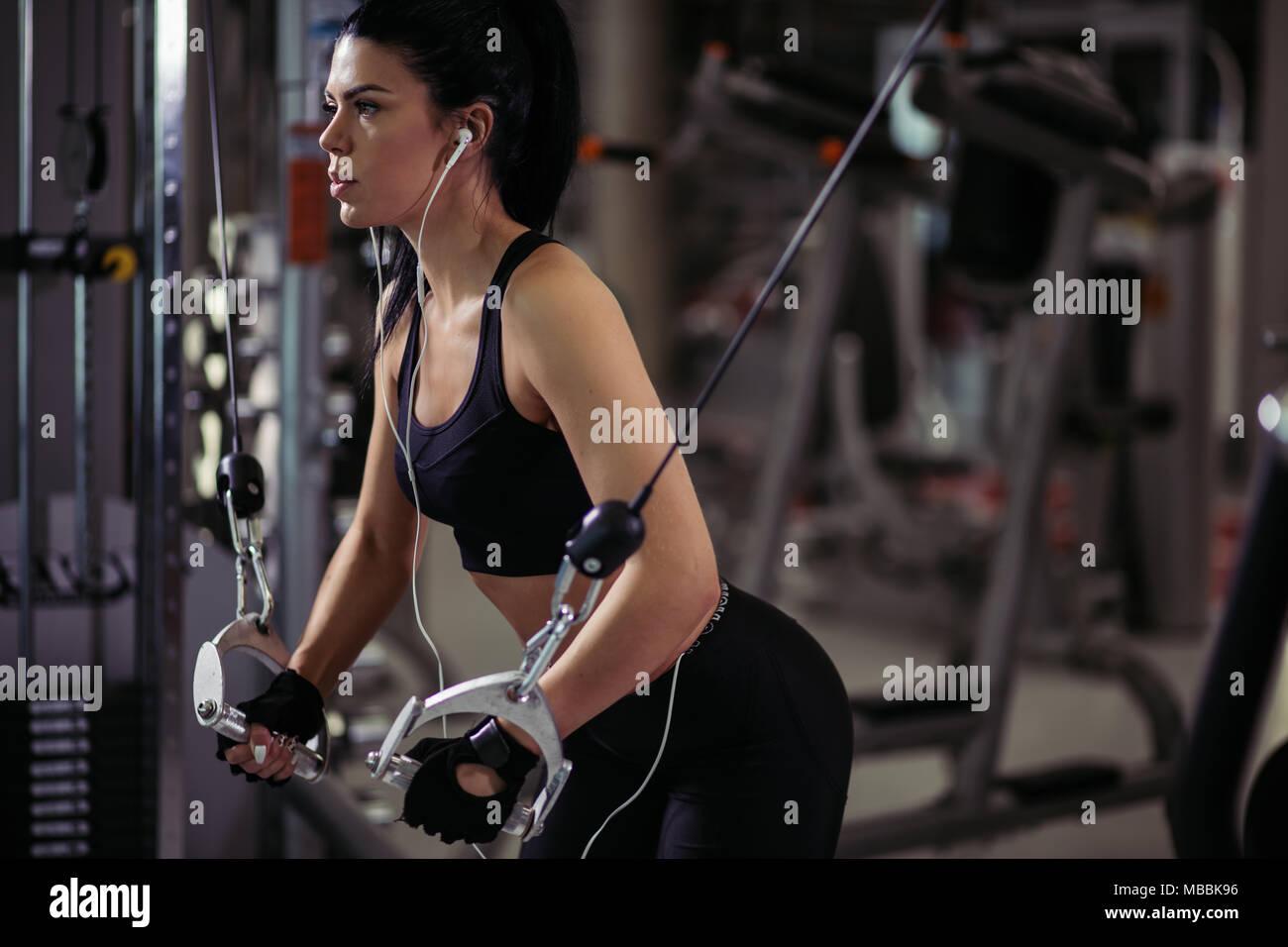 Colocar mujer ejecutar el ejercicio con máquina de ejercicio en el gimnasio Crossover Cable Imagen De Stock