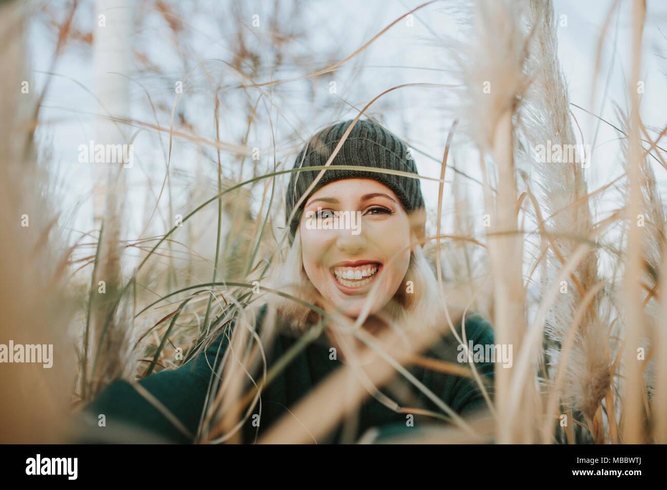 Retrato de mujer rubia feliz con un gorro tejido rodeado de reed plantas en  la naturaleza b7689d0f738