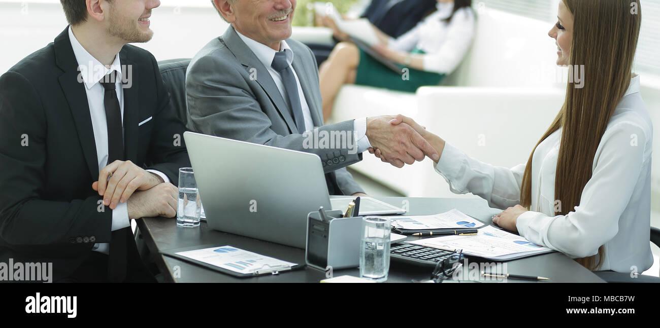 Mujer de negocios un apretón de manos con un adulto socio comercial. Imagen De Stock