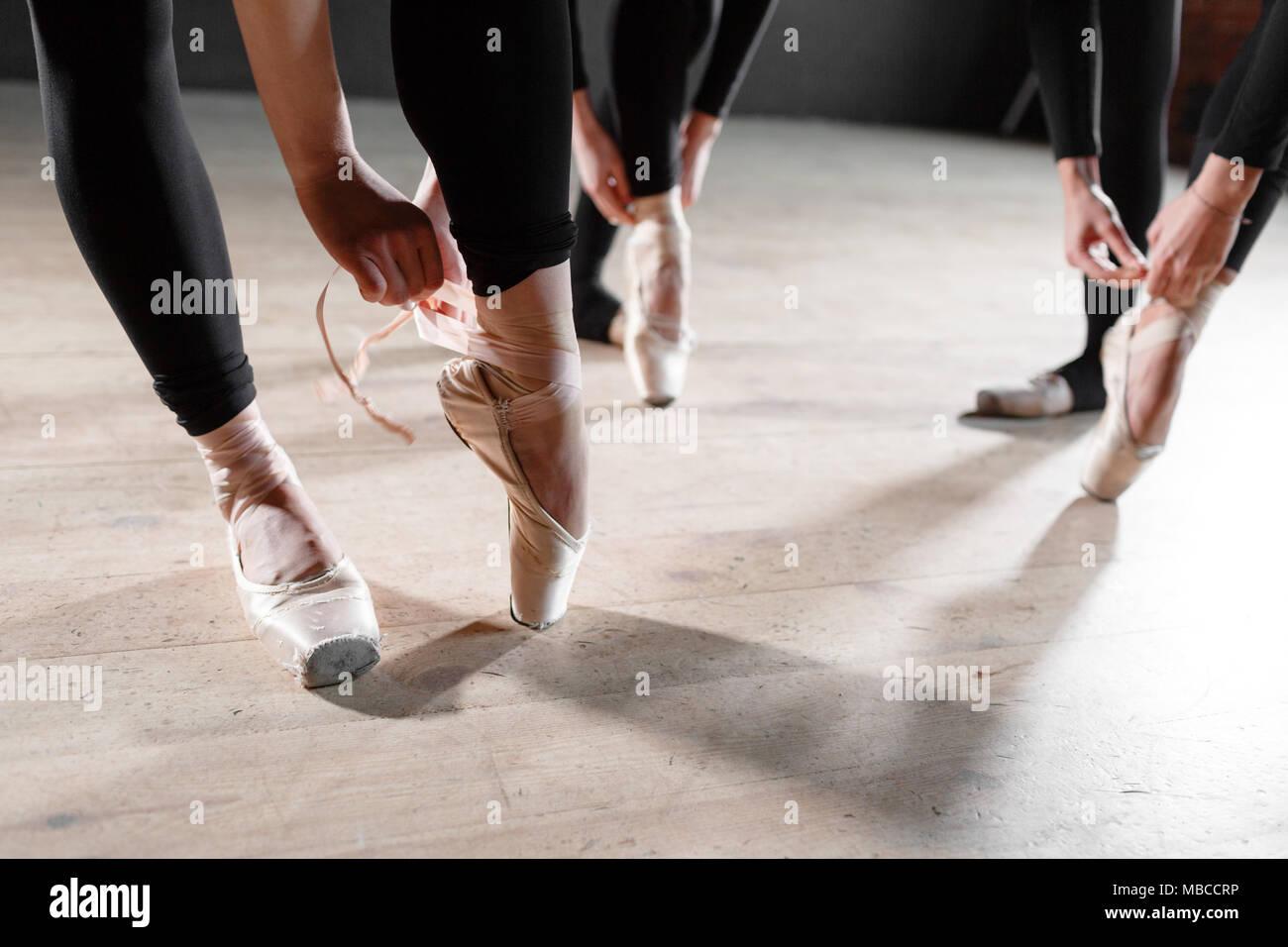 El concepto de ballet. Pointe zapatos de cerca. Joven bailarina niñas. Las mujeres en el ensayo en blanco bodysuits. Preparar una representación teatral Imagen De Stock