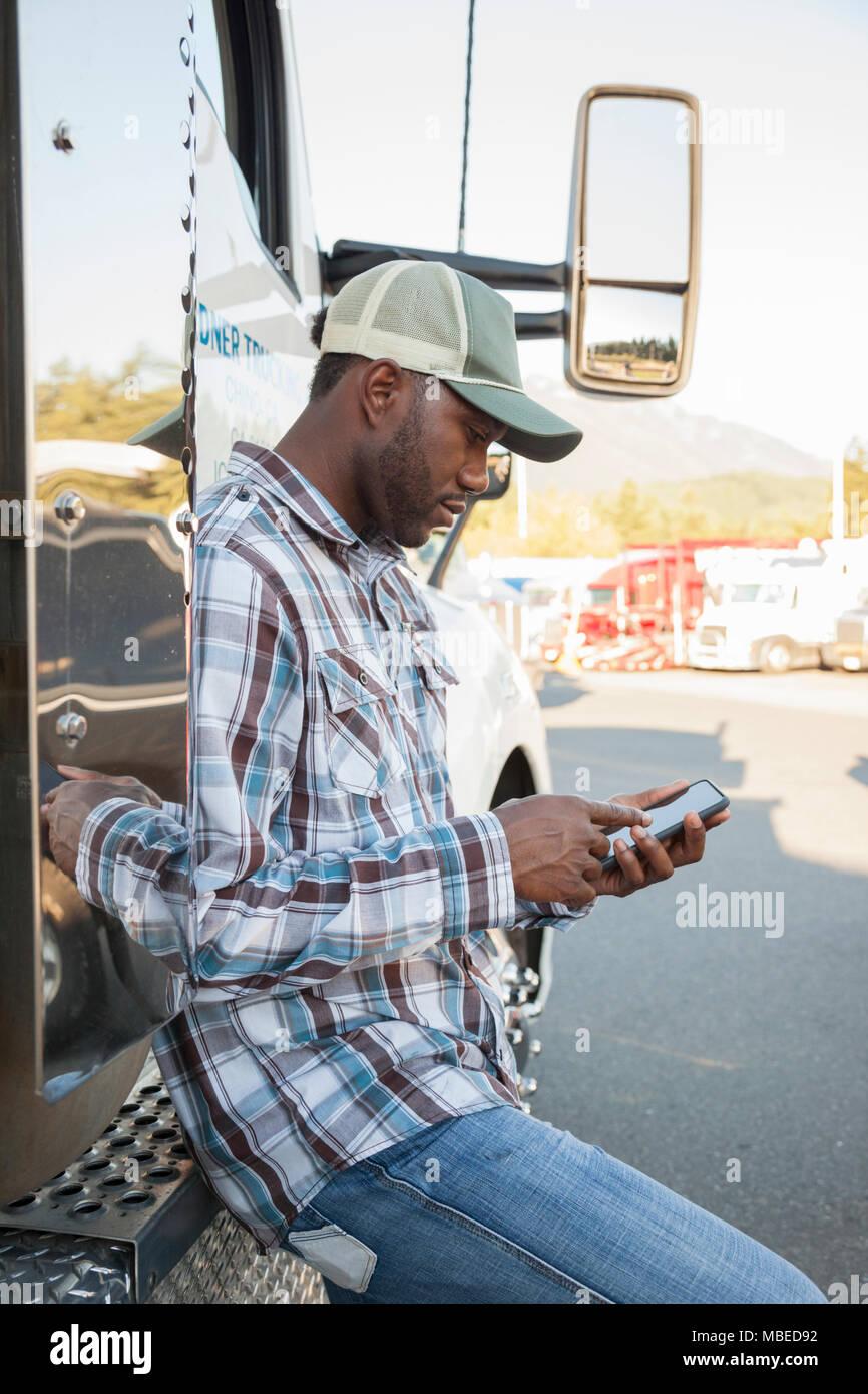 Hombre Negro camionero texting mientras está de pie junto a la cabina de su camión estacionado en un lote en una parada de camiones. Imagen De Stock