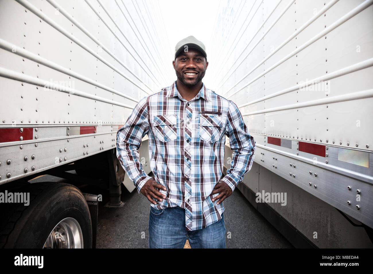 Un conductor de camión de pie entre dos grandes remolques de camiones en un trailer park, las manos en las caderas, sonriente, ropa de trabajo Imagen De Stock