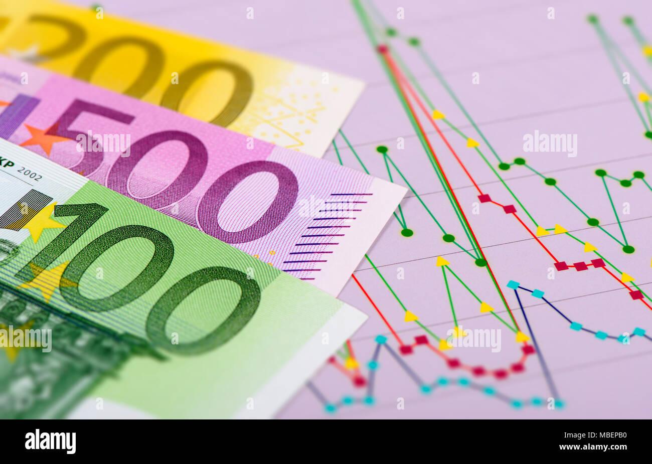 Los billetes de la moneda europea sentando en el gráfico del mercado de valores Imagen De Stock