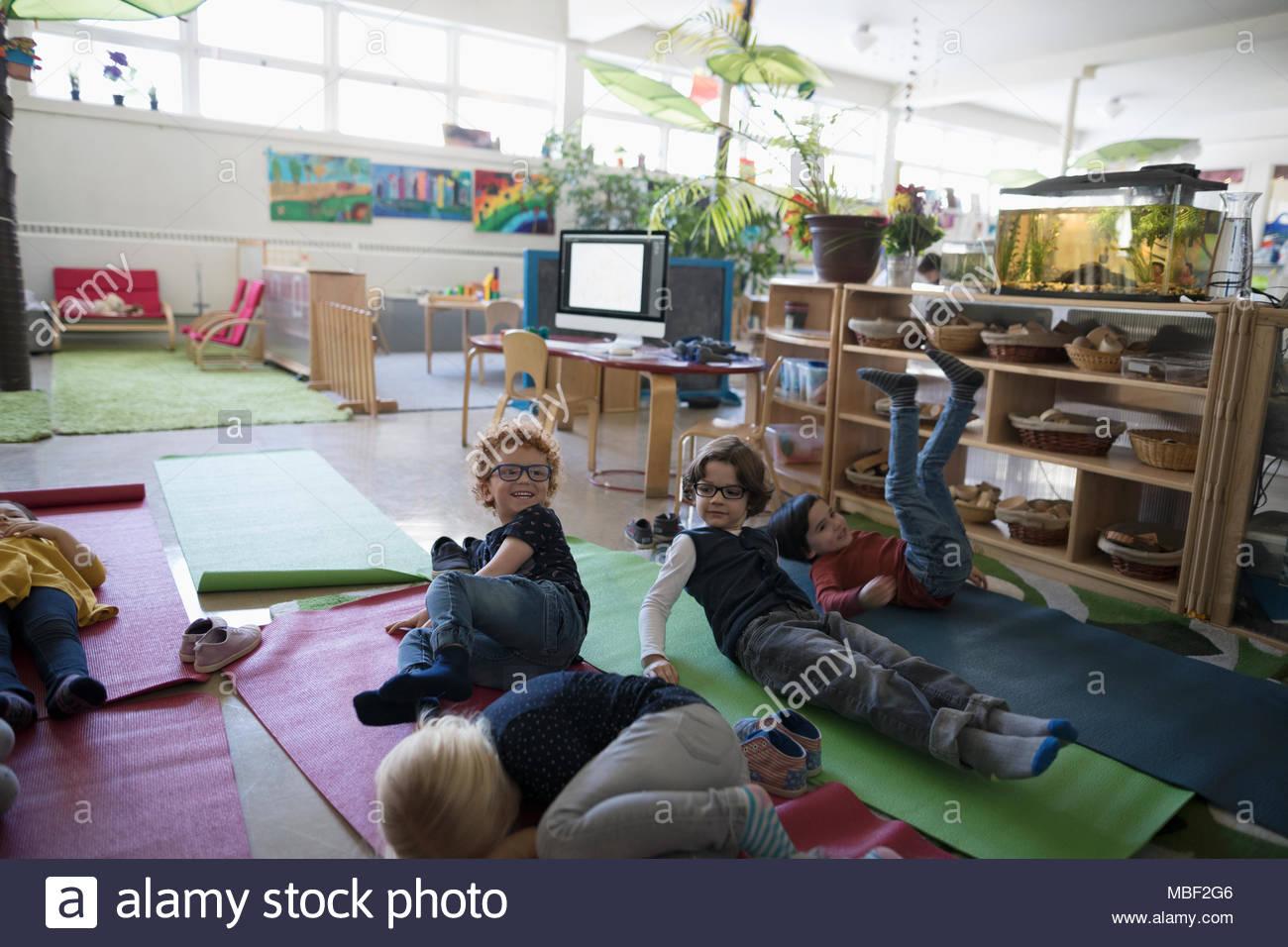 Cansados los estudiantes preescolares descansando en las esteras del yoga durante la hora de la siesta Imagen De Stock