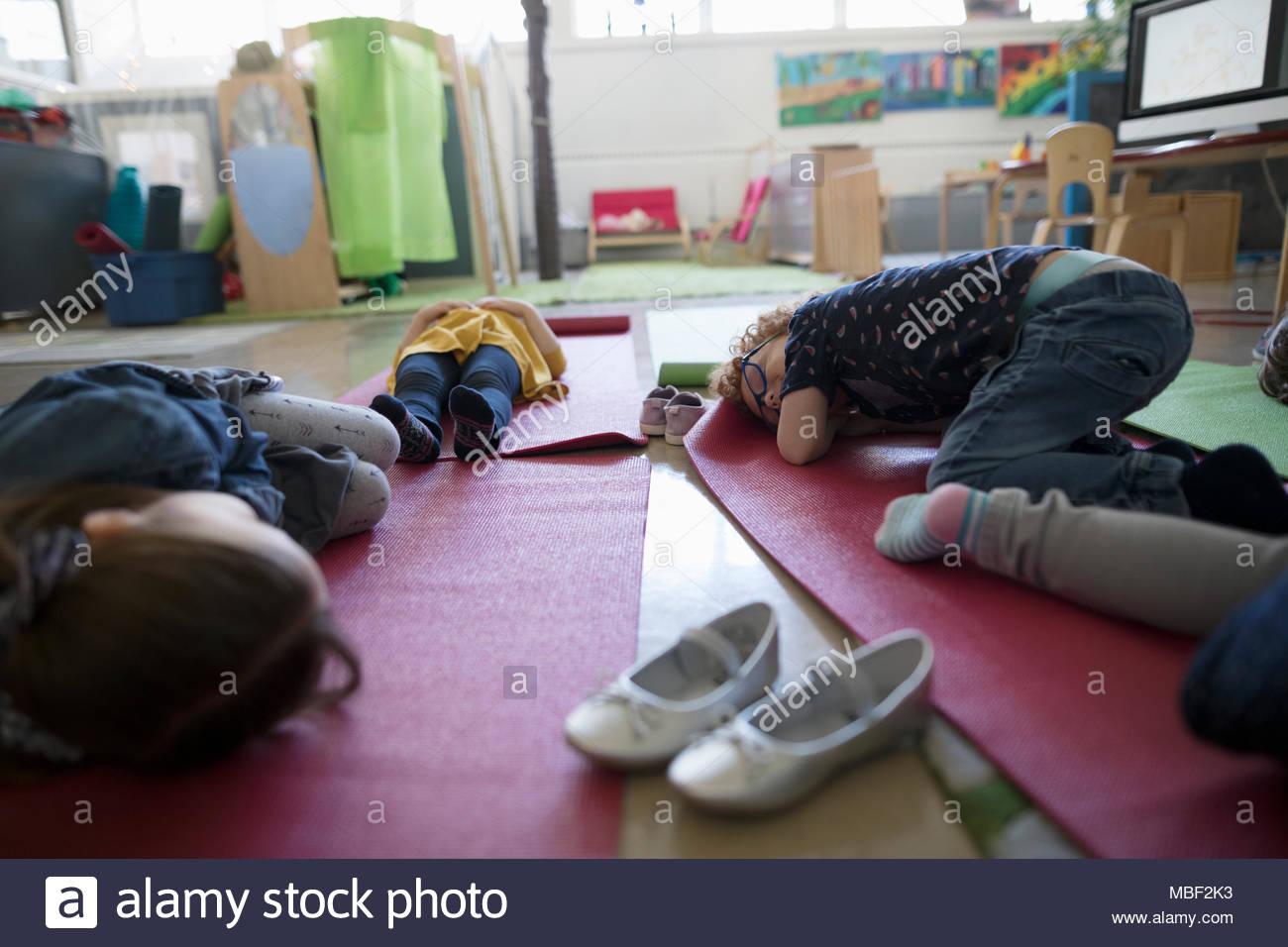 Cansados los estudiantes preescolares duermen en colchonetas para yoga durante la hora de la siesta Imagen De Stock