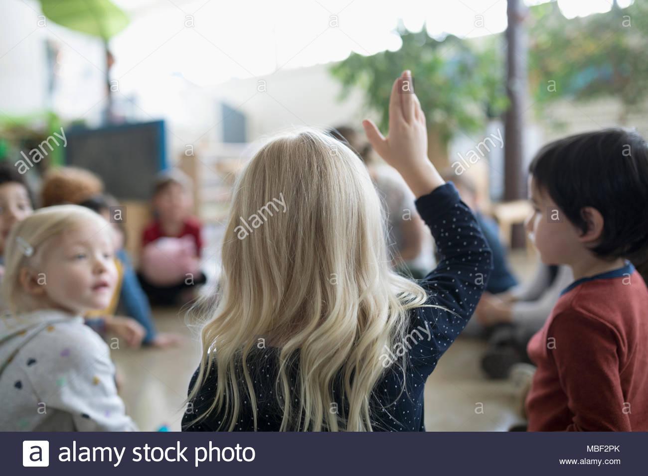 Niña preescolar estudiante levantando la mano en el aula Imagen De Stock
