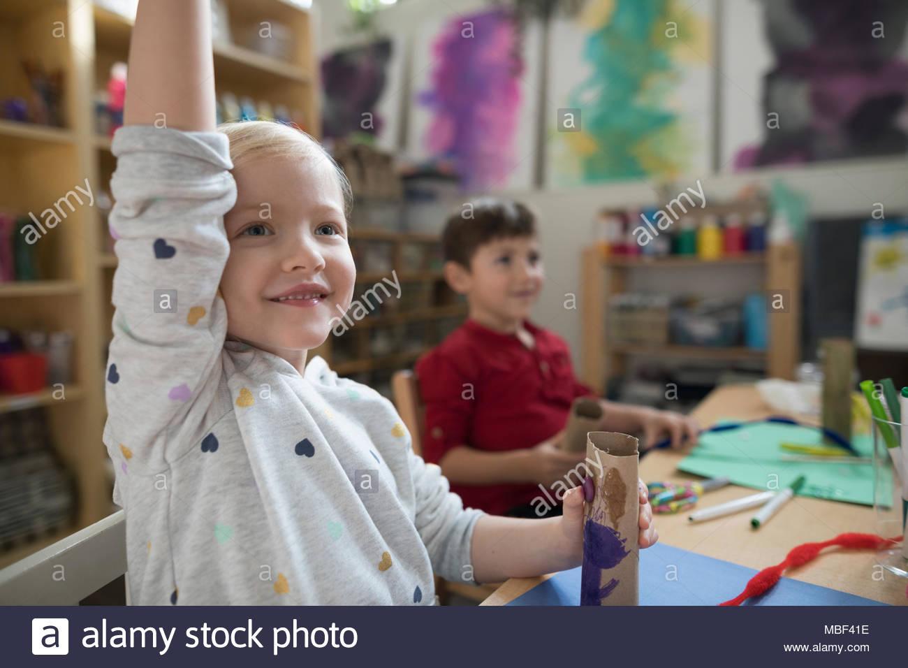 Ansiosa Niña preescolar levantando la mano en la clase de arte Imagen De Stock