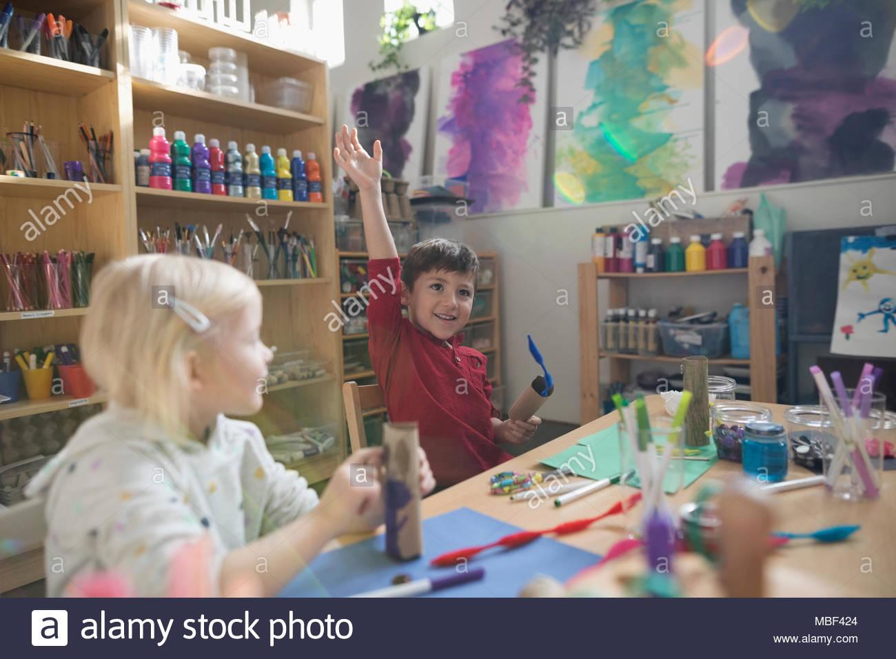 Preescolar impaciente Joven levantando la mano en la clase de arte Imagen De Stock