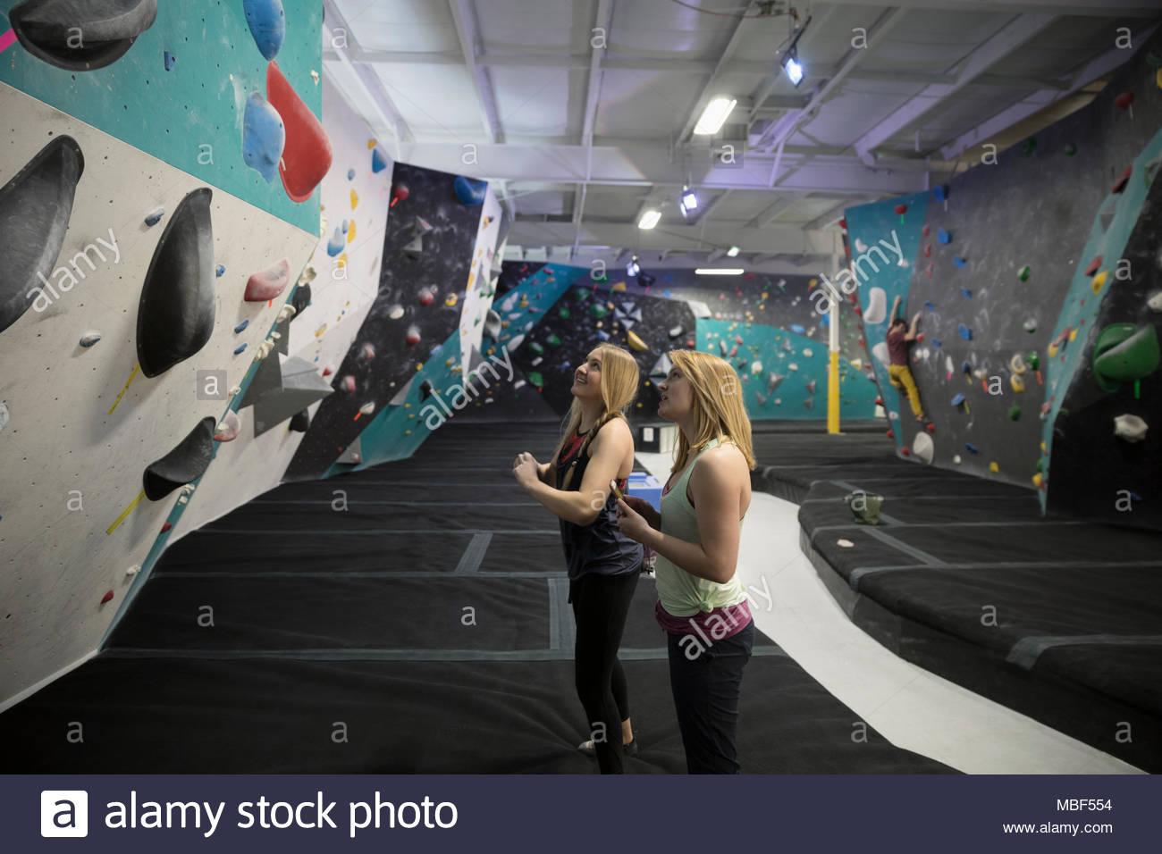 Escaladores hembra mirando hacia arriba en la pared de escalada en el gimnasio de escalada Imagen De Stock