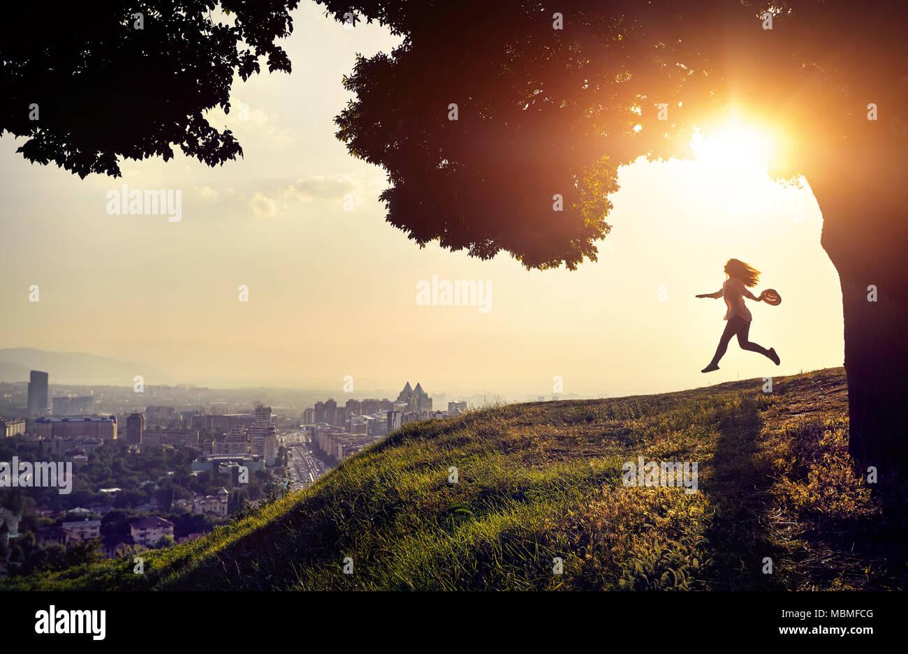 Mujer en silueta corriendo con el sombrero en la mano en el fondo de la vista de la ciudad al atardecer. Concepto de la vida de la ciudad. Imagen De Stock