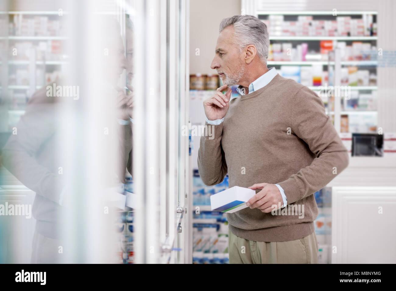 Apuesto hombre senior eligiendo vitaminas Imagen De Stock