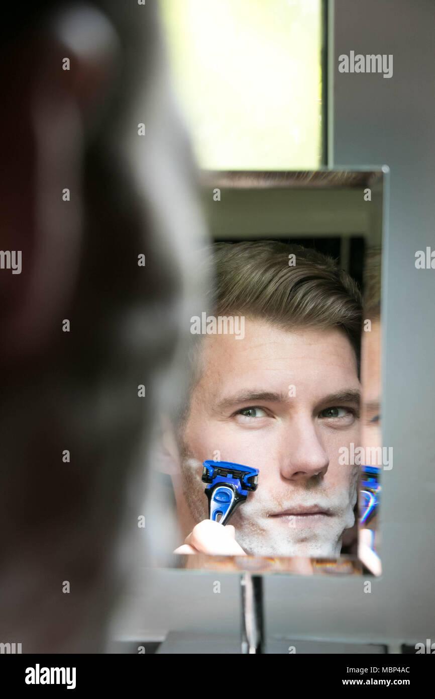 Reflejo de guapo con ojos verdes se afeita con la afeitadora en azul espejo pequeño Imagen De Stock