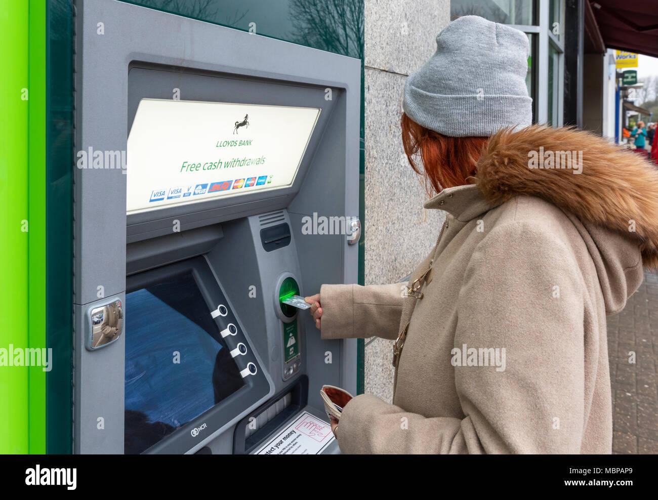 Mujer Senior sacar dinero de un cajero automático de Lloyds Bank en Inglaterra, Reino Unido. Cajeros, cajeros, cajeros automáticos, el agujero en la pared. Retiro de dinero. Imagen De Stock