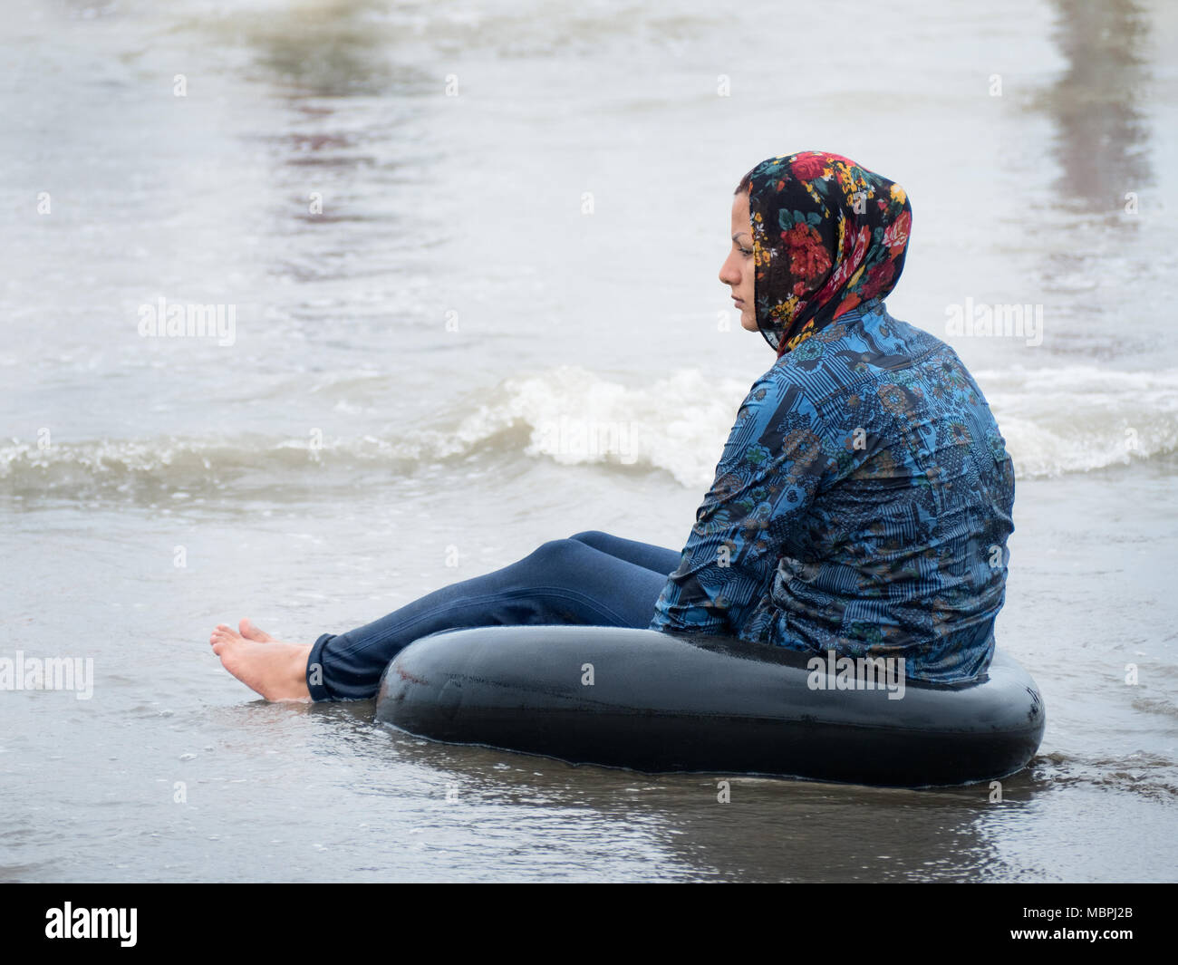 Babolsar, Irán - Julio 24, 2016 : completamente vestidos niña - de acuerdo con las normas islámicas - remando en el mar Caspio Imagen De Stock