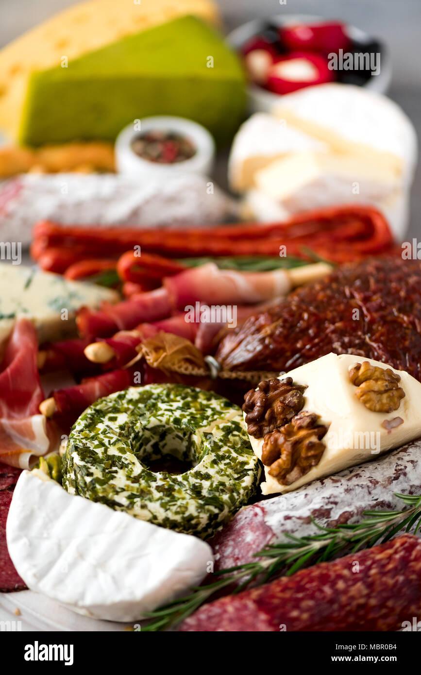 Antipasto italiano tradicional, la tabla de cortar con salami, fría la carne ahumada, Jamón, jamón, queso, aceitunas, alcaparras sobre fondo gris. Aperitivo de queso y carne. Imagen De Stock