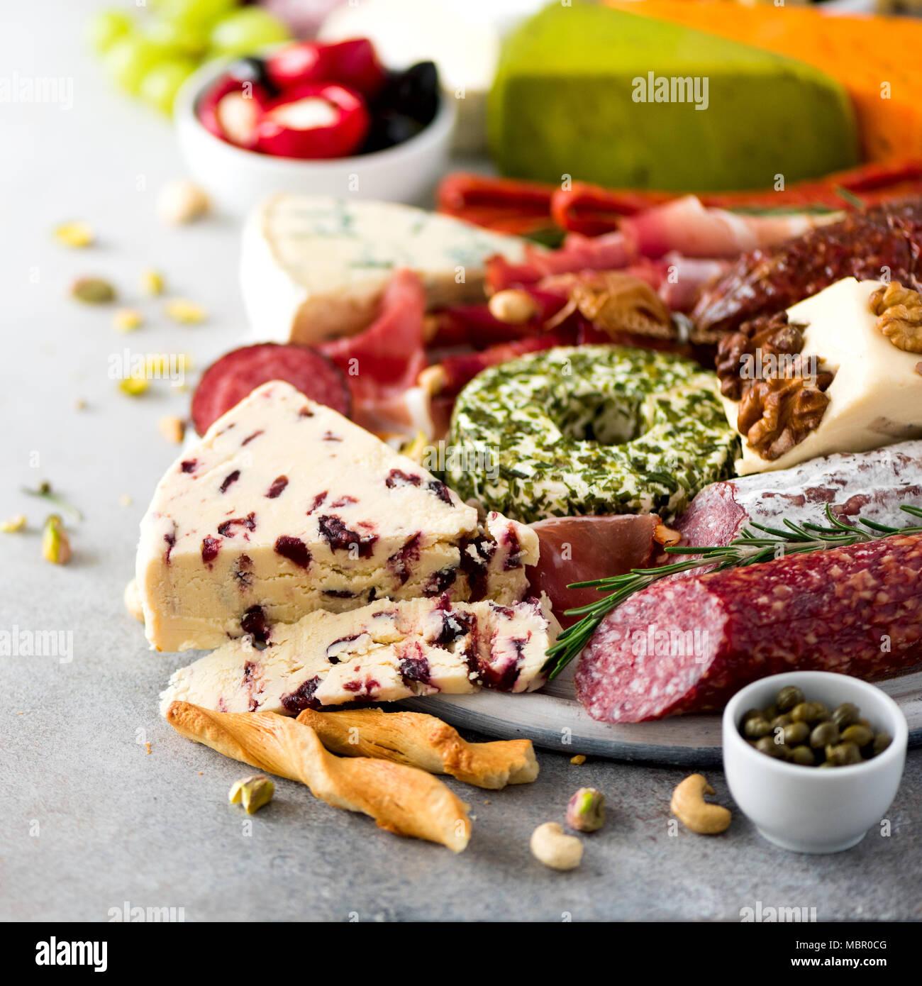 Antipasto italiano tradicional, la tabla de cortar con salami, fría la carne ahumada, Jamón, jamón, queso, aceitunas, alcaparras sobre fondo gris. Aperitivo de queso y carne. Recortar cuadrados Foto de stock