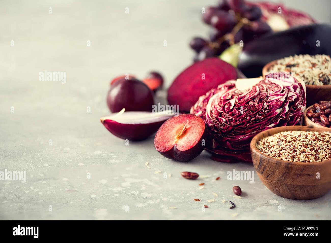 Ingredientes para cocinar, copie el espacio, vista superior, plano laical. Las verduras, las frutas púrpura sobre fondo gris. Violeta berenjena, remolacha, coliflor, violeta, frijoles, ciruelas, cebolla, uva, quinoa, arroz. Imagen De Stock