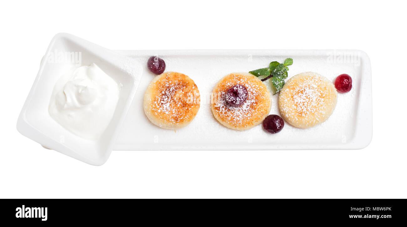 Queso tortitas aislado vista desde arriba. Requesón panqueques con crema agria y cherry Foto de stock