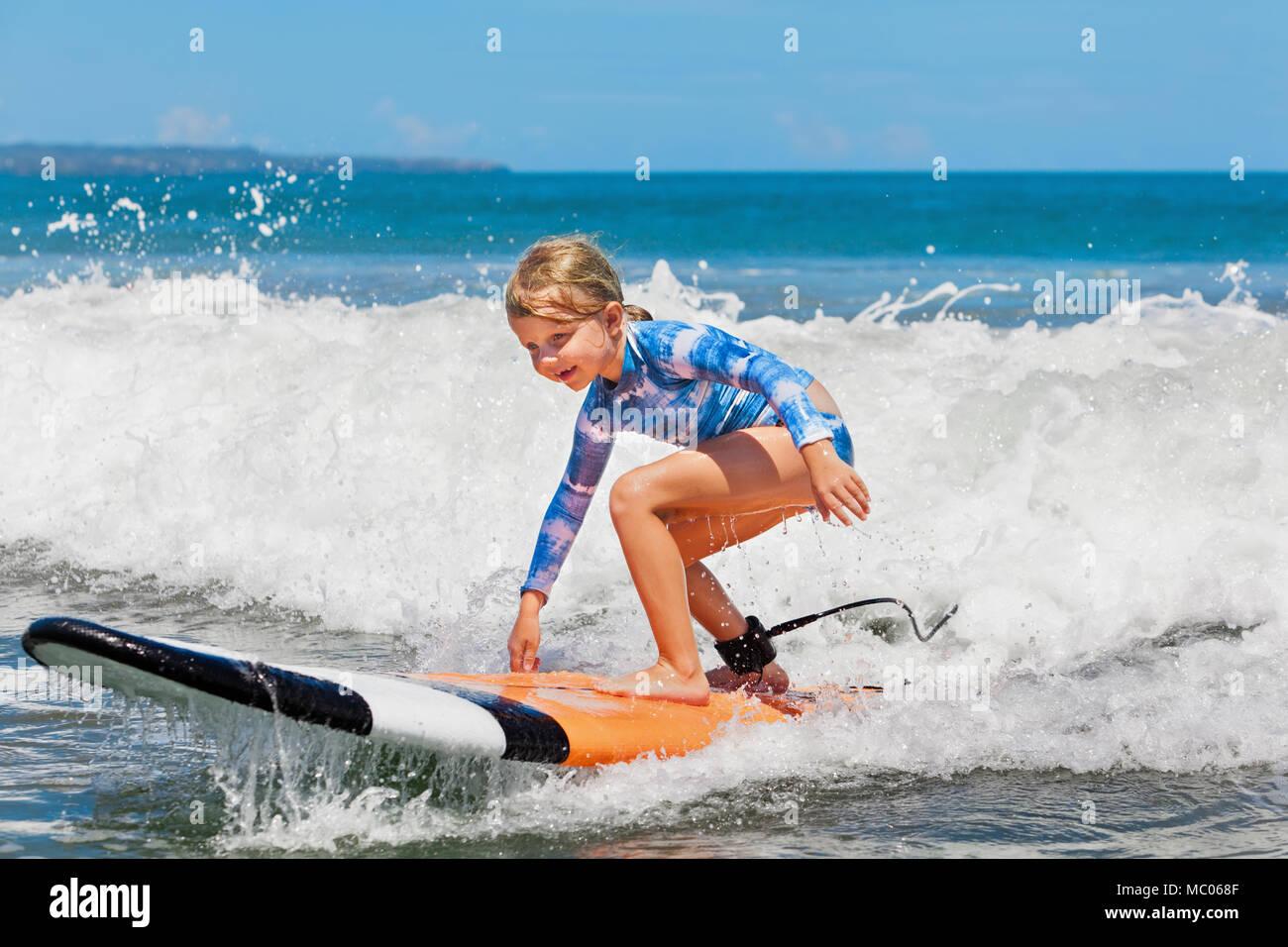 Niña feliz - joven surfista paseo en tablas de surf con diversión en Mar Ola activo estilo de vida familiar, los niños piscina deporte acuático lecciones y actividades en la playa Imagen De Stock