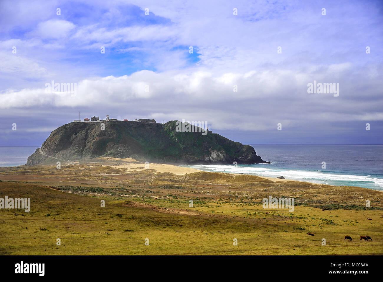 La pintoresca escena de faro de Point Sur Cabrillo Highway con césped verde en primer plano, mar turquesa y cielo nublado Imagen De Stock