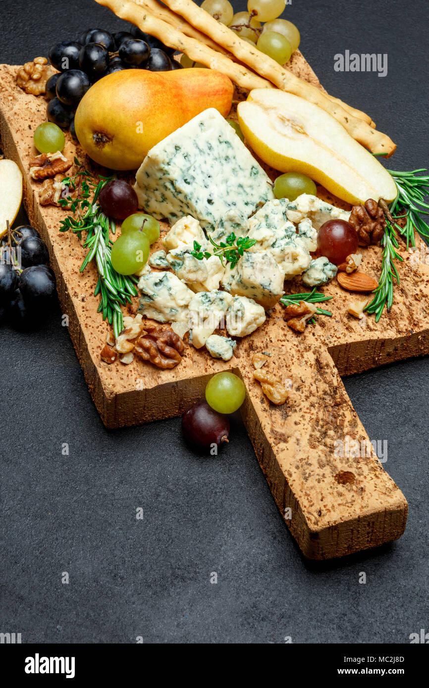 Peras y queso en la placa de corte de madera Imagen De Stock