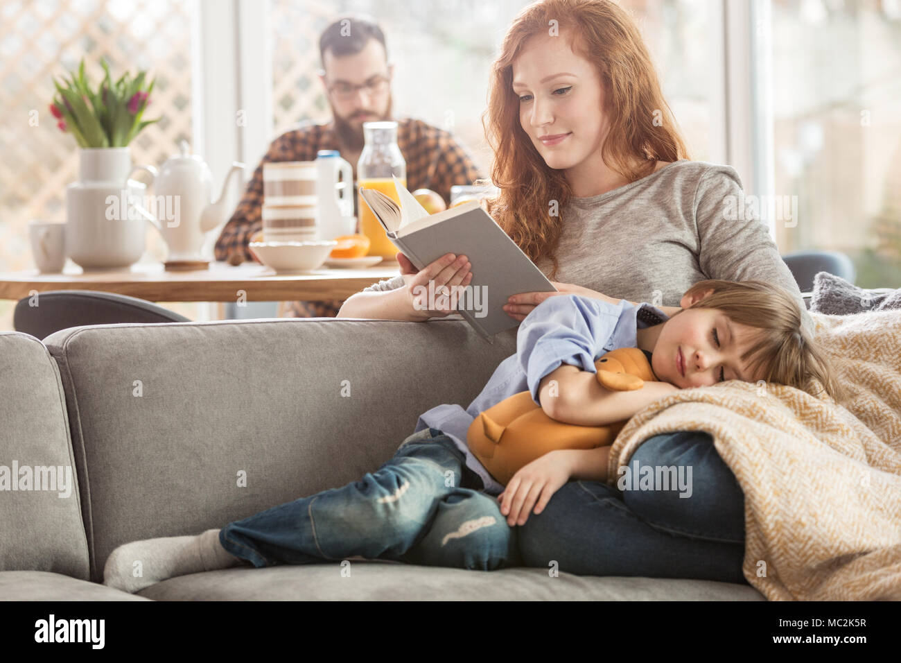 Hijo dormido acostado en el regazo de la madre mientras ella está leyendo un libro y padre comiendo en el fondo Foto de stock