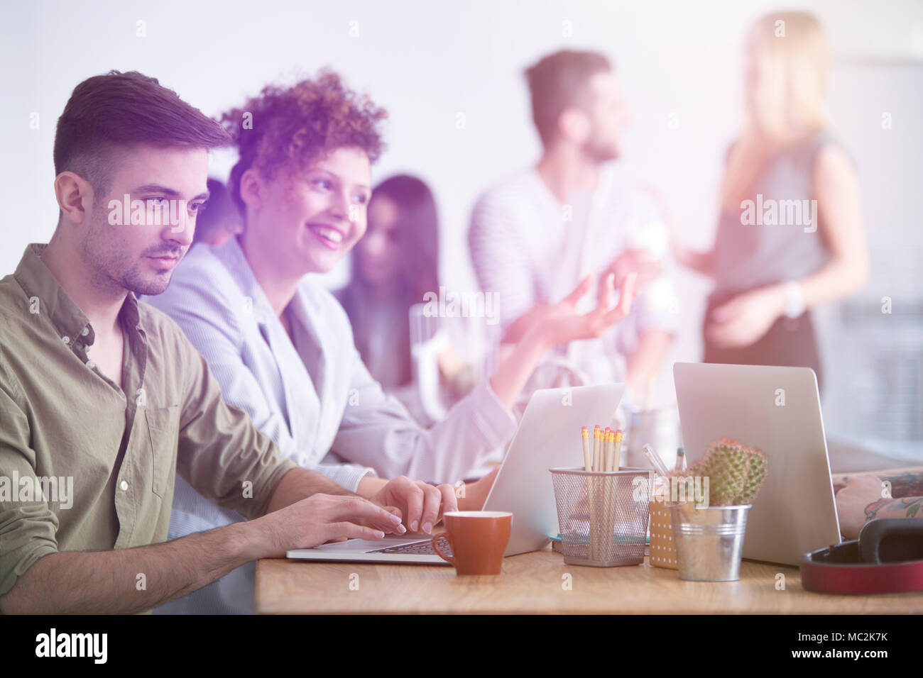 Un empresario trabajando en su computadora portátil y su mujer sonriendo y hablando junto a él Foto de stock