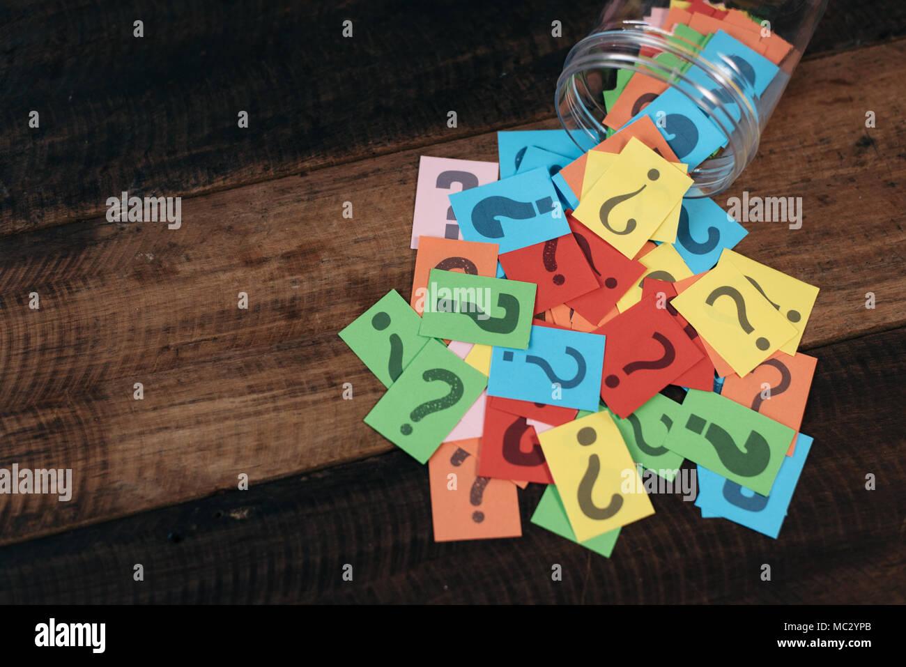 Colorido papel con signo de interrogación en una jarra de plástico sobre la mesa de madera. preguntas y el concepto de la diversidad. FAQ y Q&Un concepto de fondo Imagen De Stock