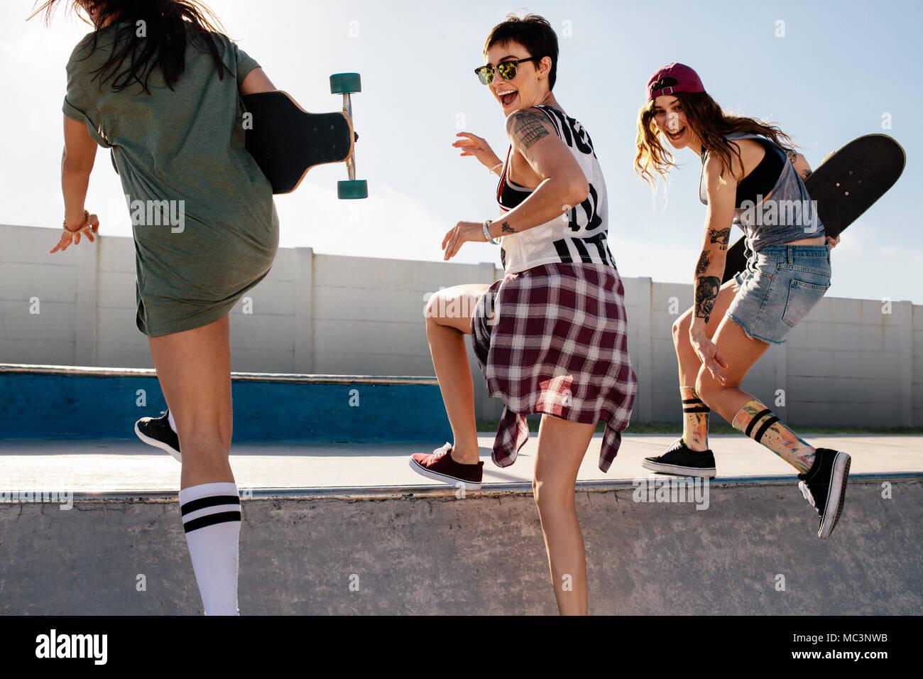 Laughing mujer subiendo una rampa de skate con los amigos. El grupo de  niñas teniendo daa9907414e