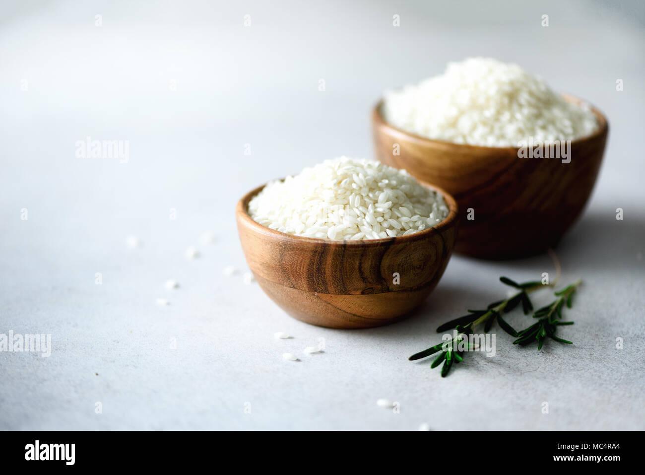 Raw blanco arroz jazmín orgánico en Wooden bowl y el romero en el hormigón ligero trasfondo. Los ingredientes de los alimentos. Espacio de copia Imagen De Stock