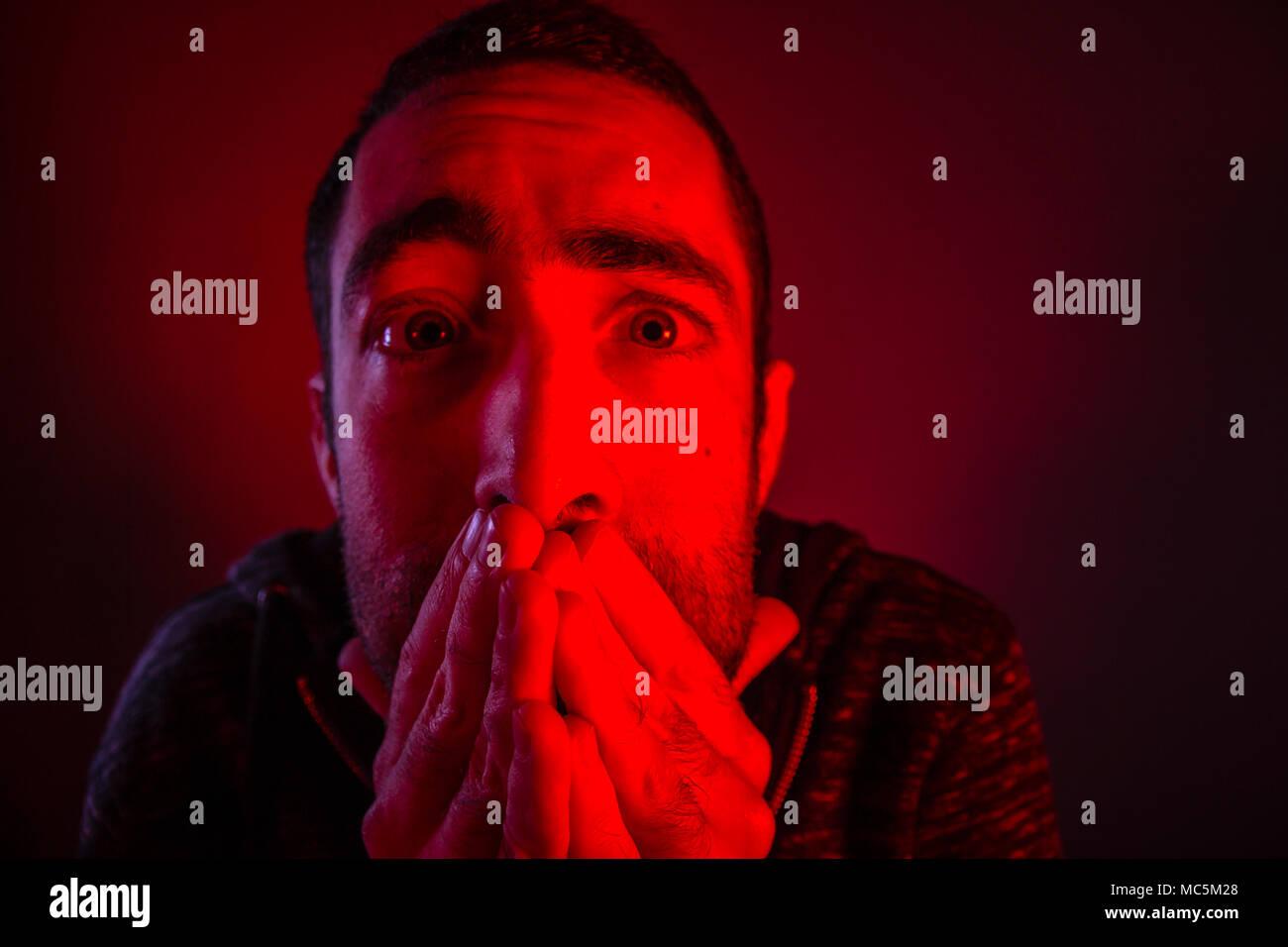 Aturdido hombre asustado con sorpresa la expresión facial. Cerrar headshot retrato de consternado al hombre con su mano en la cara. Imagen De Stock