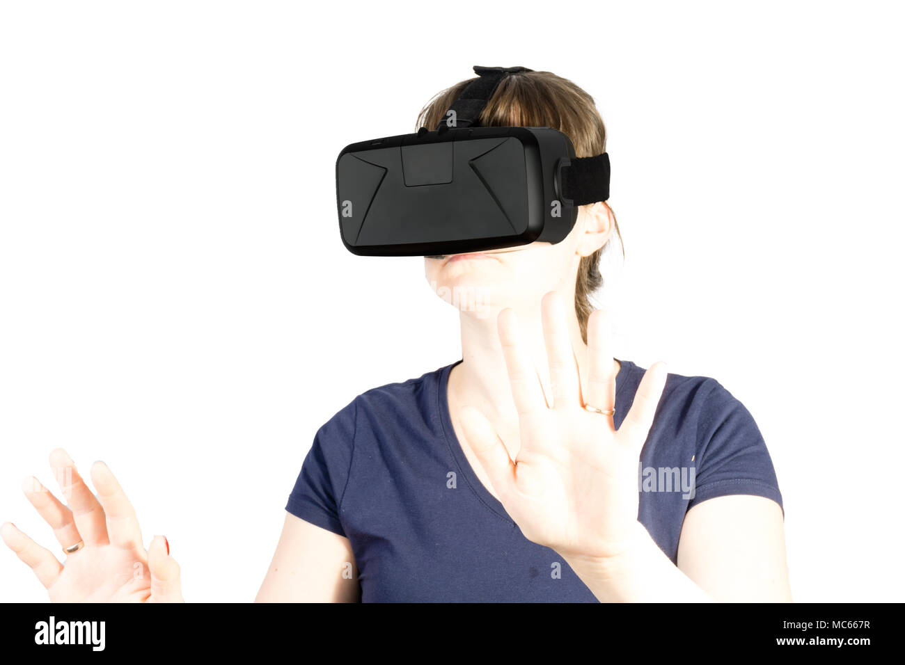 Atractiva mujer joven ajustando su auricular VR. Aislado sobre fondo blanco. Imagen De Stock