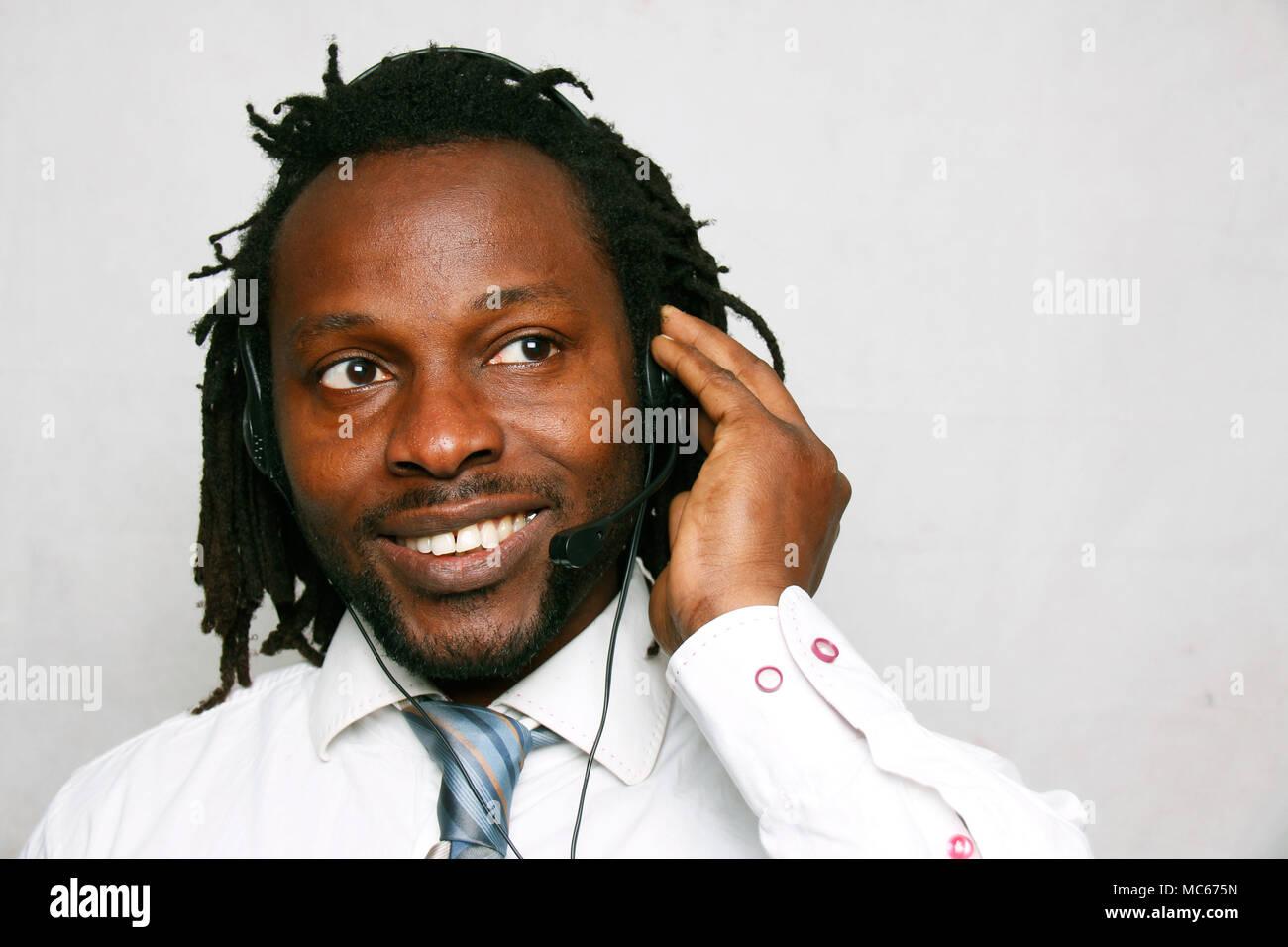 Un hombre de negocios sonriendo sonriendo y llamando con los auriculares, el servicio de atención al cliente Foto de stock