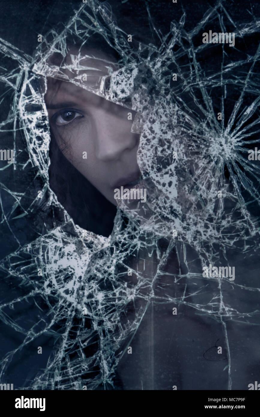 Primer plano de una joven mujer caucásica mirando desde detrás de un cristal roto, conceptual espectacular retrato. Imagen De Stock