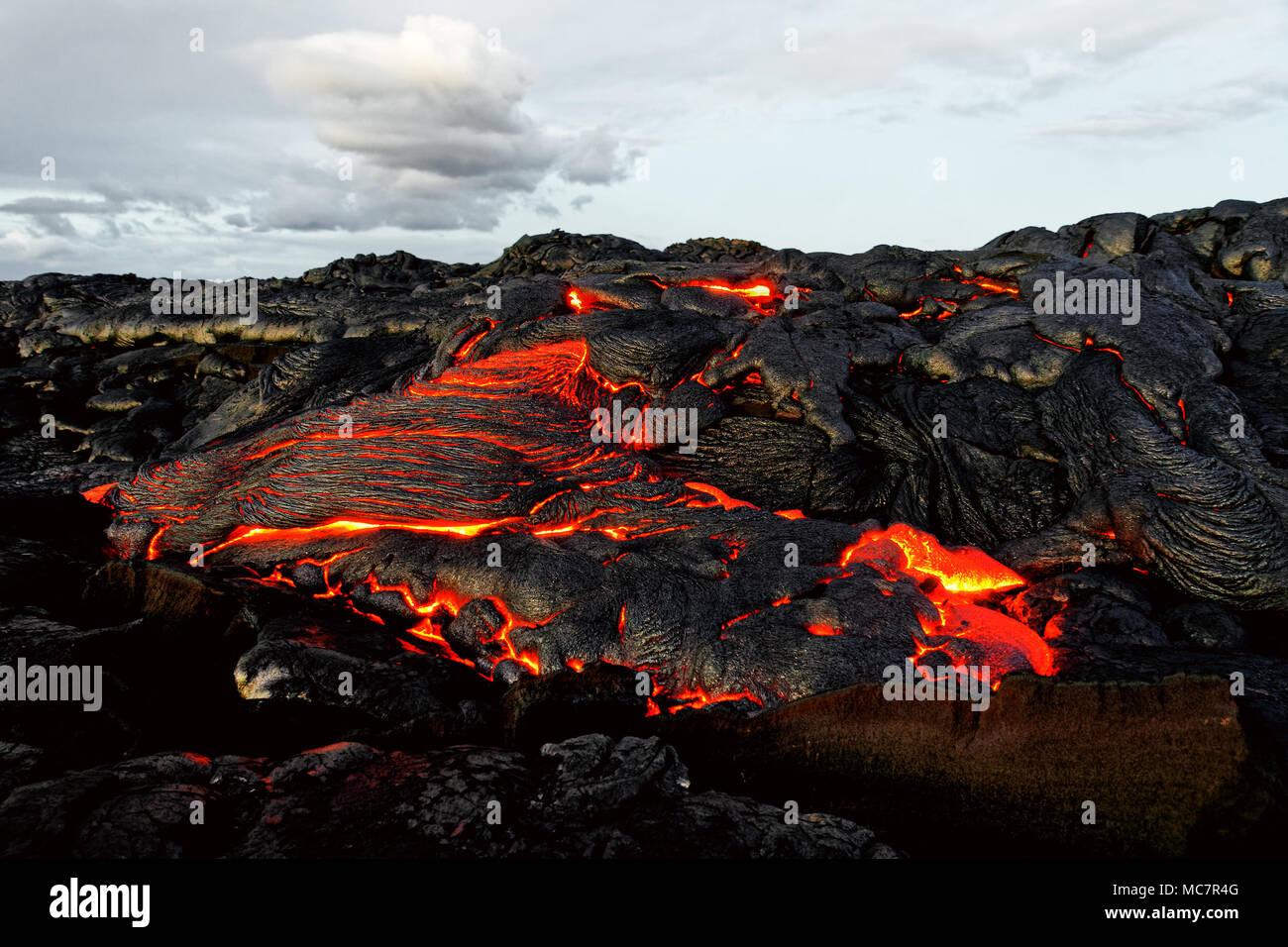 Un flujo de lava emerge de una masa de columna y fluye en un paisaje volcánico negro, en el cielo muestra el primer día - Ubicación: Hawai, Isla Grande, Imagen De Stock