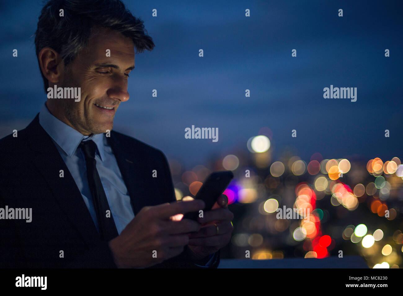 Empresario de gran altura a través de teléfono móvil en la azotea Imagen De Stock