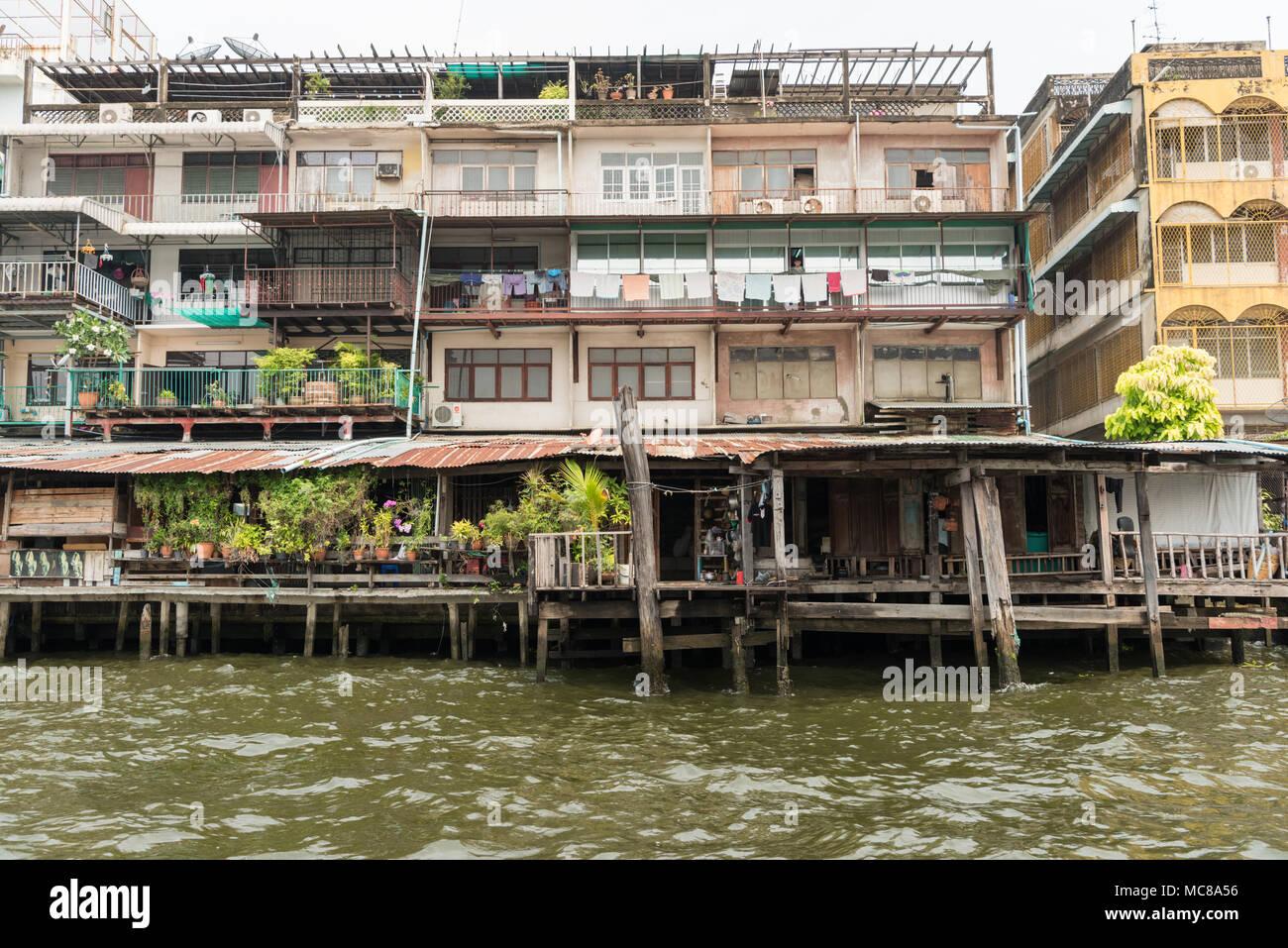 Destartalado construcciones hechas de madera y hierro corrugado junto al río Chao Phraya, en Bangkok, Tailandia Imagen De Stock