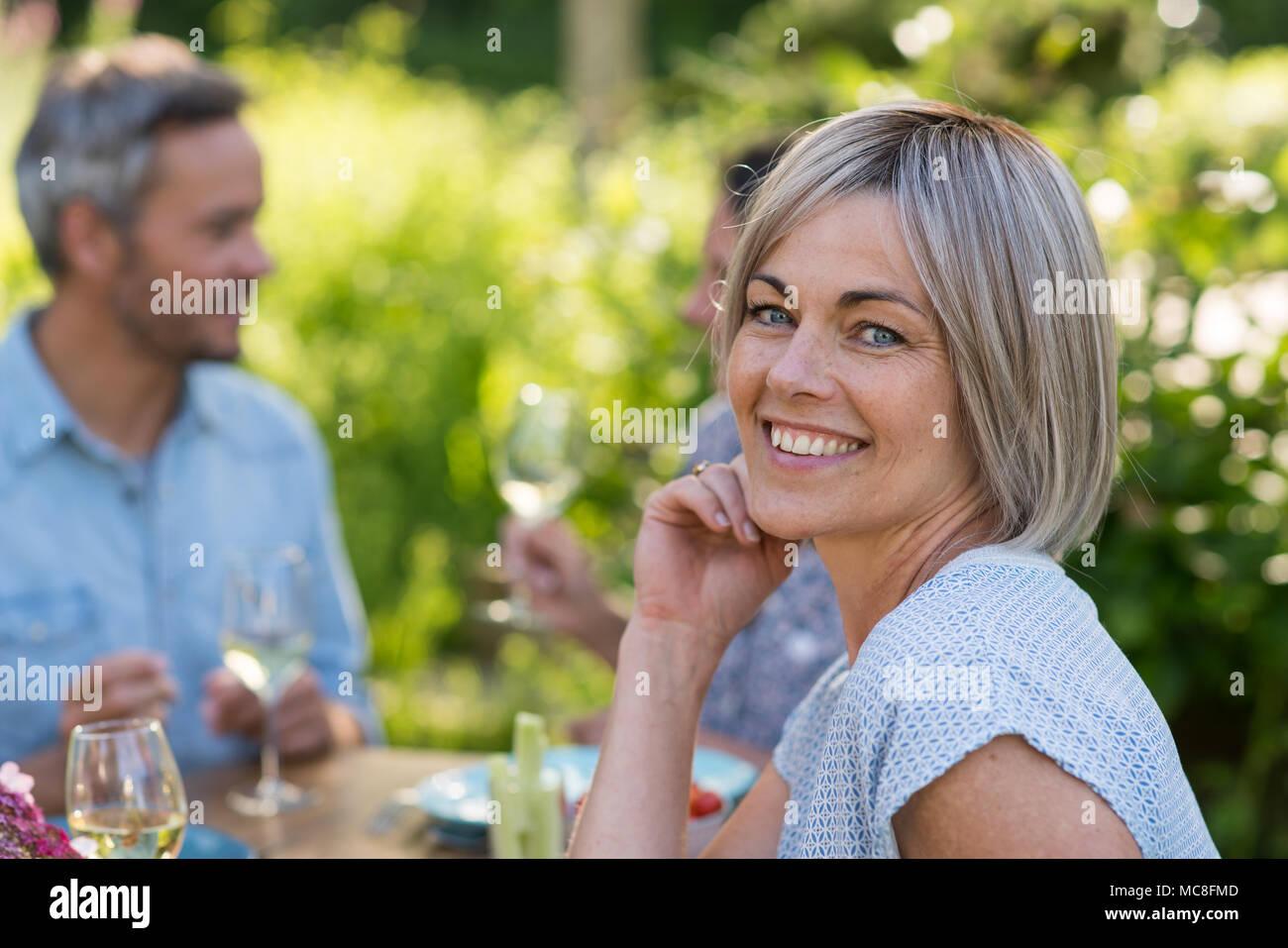 Un grupo de amigos se reunieron para compartir una comida alrededor de una mesa en el jardín. Se centran en una hermosa mujer mirando la cámara Imagen De Stock
