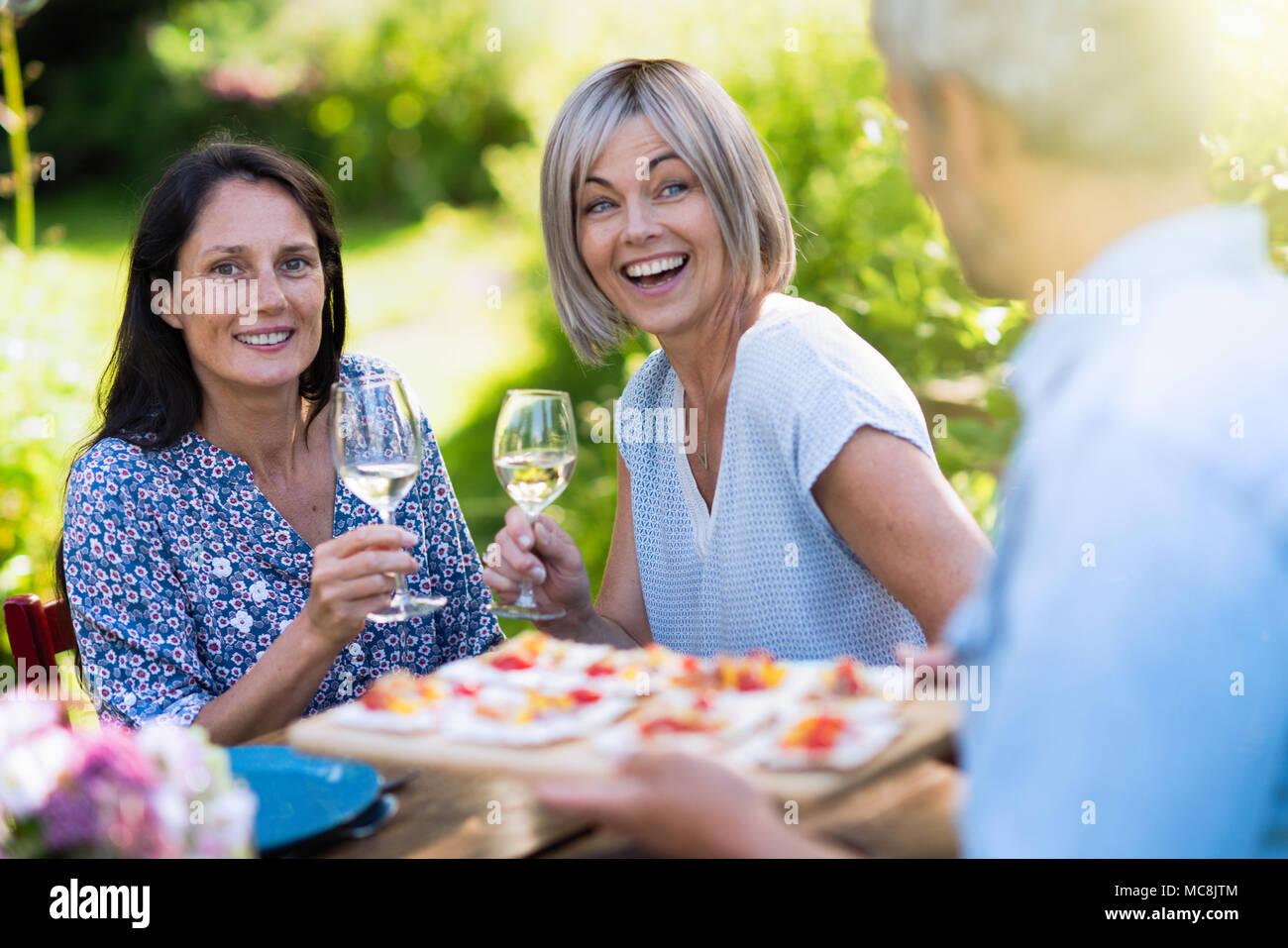 Grupo de amigos en sus cuarenta, reunidos alrededor de una mesa en el jardín para compartir una comida. Un hombre ofrece aperitivos para los huéspedes Imagen De Stock