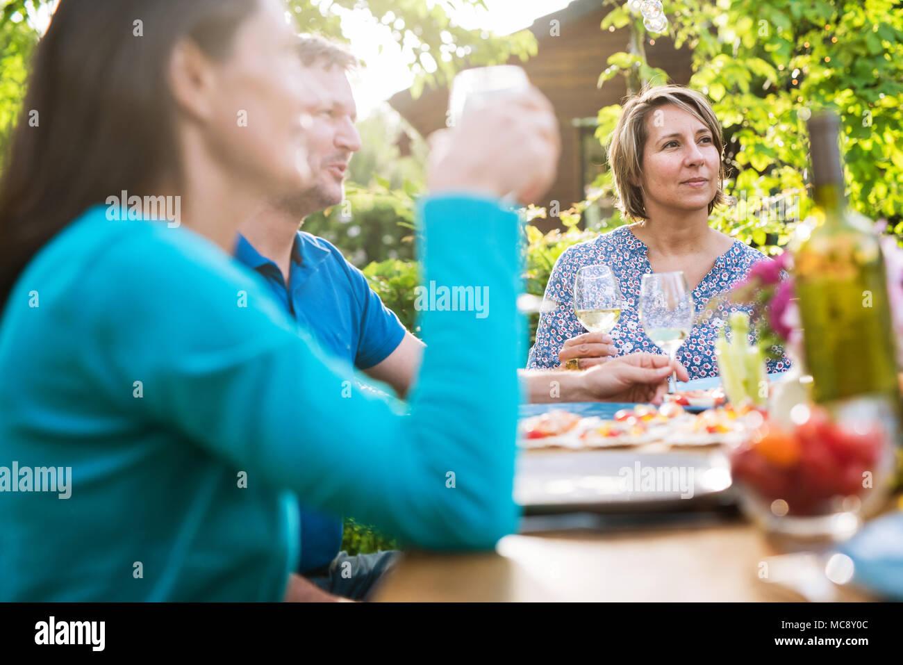 Amigos reunidos alrededor de una mesa en el jardín una noche de verano para compartir una comida y divertirse juntos. Imagen De Stock
