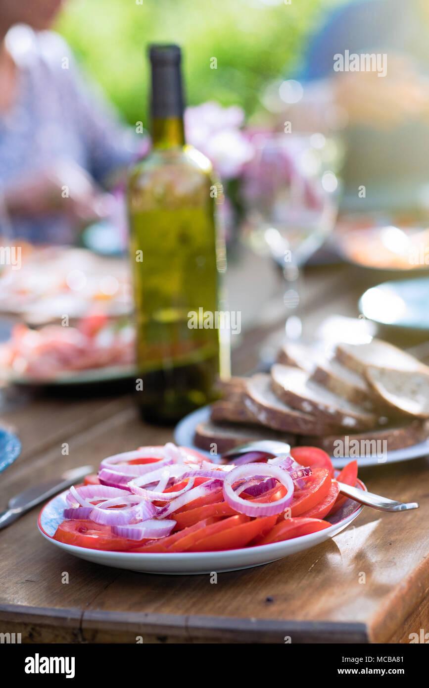 Cerca en una placa con tomate y cebolla en rodajas sobre una tabla en un jardín, donde los amigos se reúnen para compartir una comida. Imagen De Stock