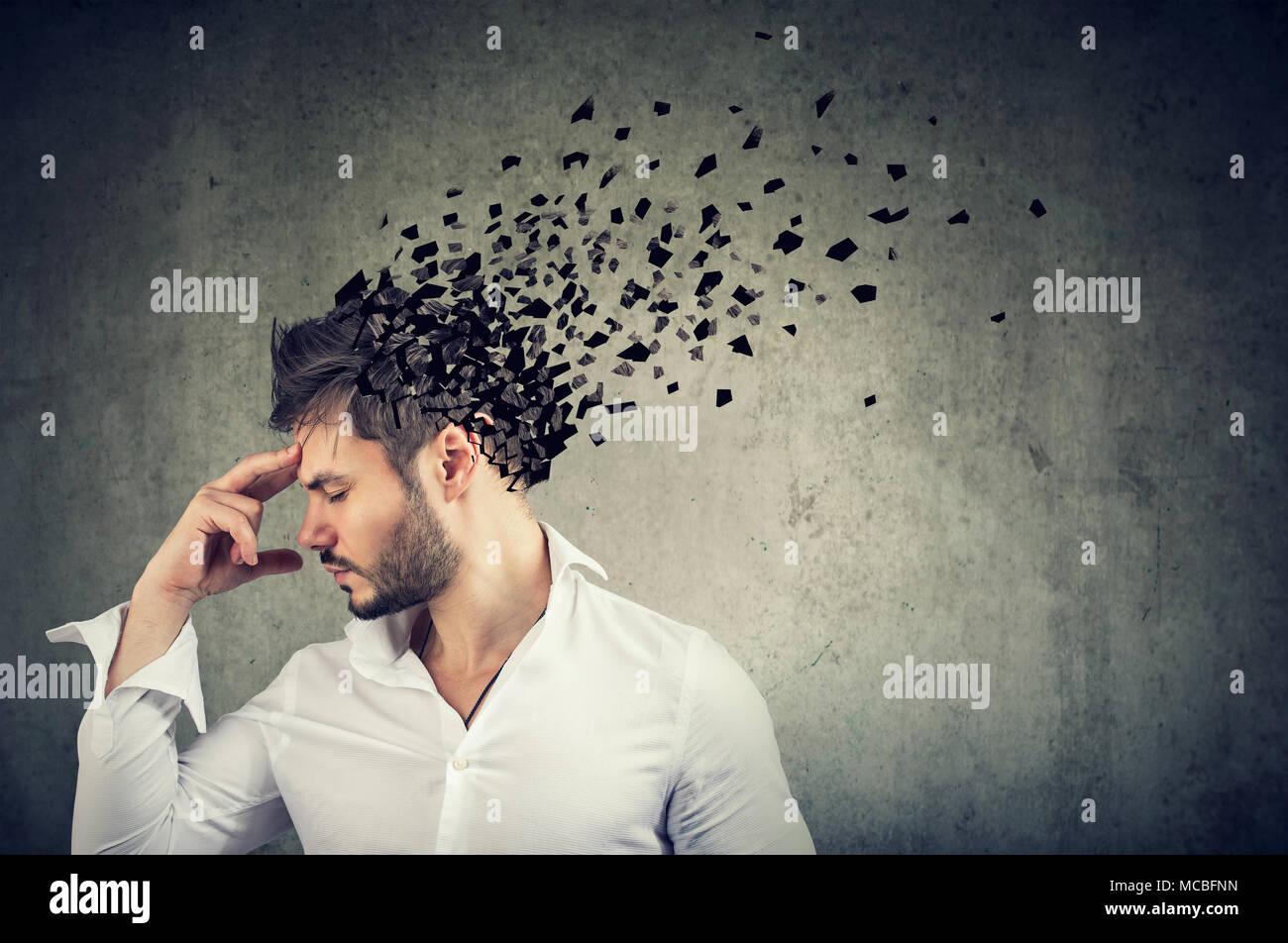 La pérdida de memoria debido a la demencia o daño cerebral. El perfil lateral de un hombre perder partes de cabeza como símbolo de disminución de la función de la mente. Imagen De Stock