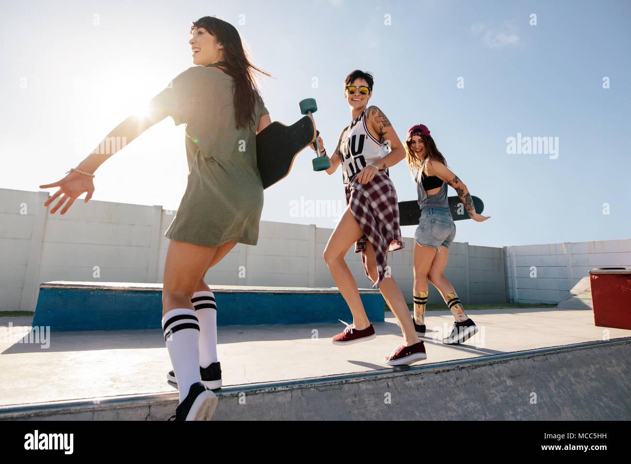 Tres amigas correr y saltar sobre la rampa de skate park. Las mujeres  skaters disfrutan 655ca793afc