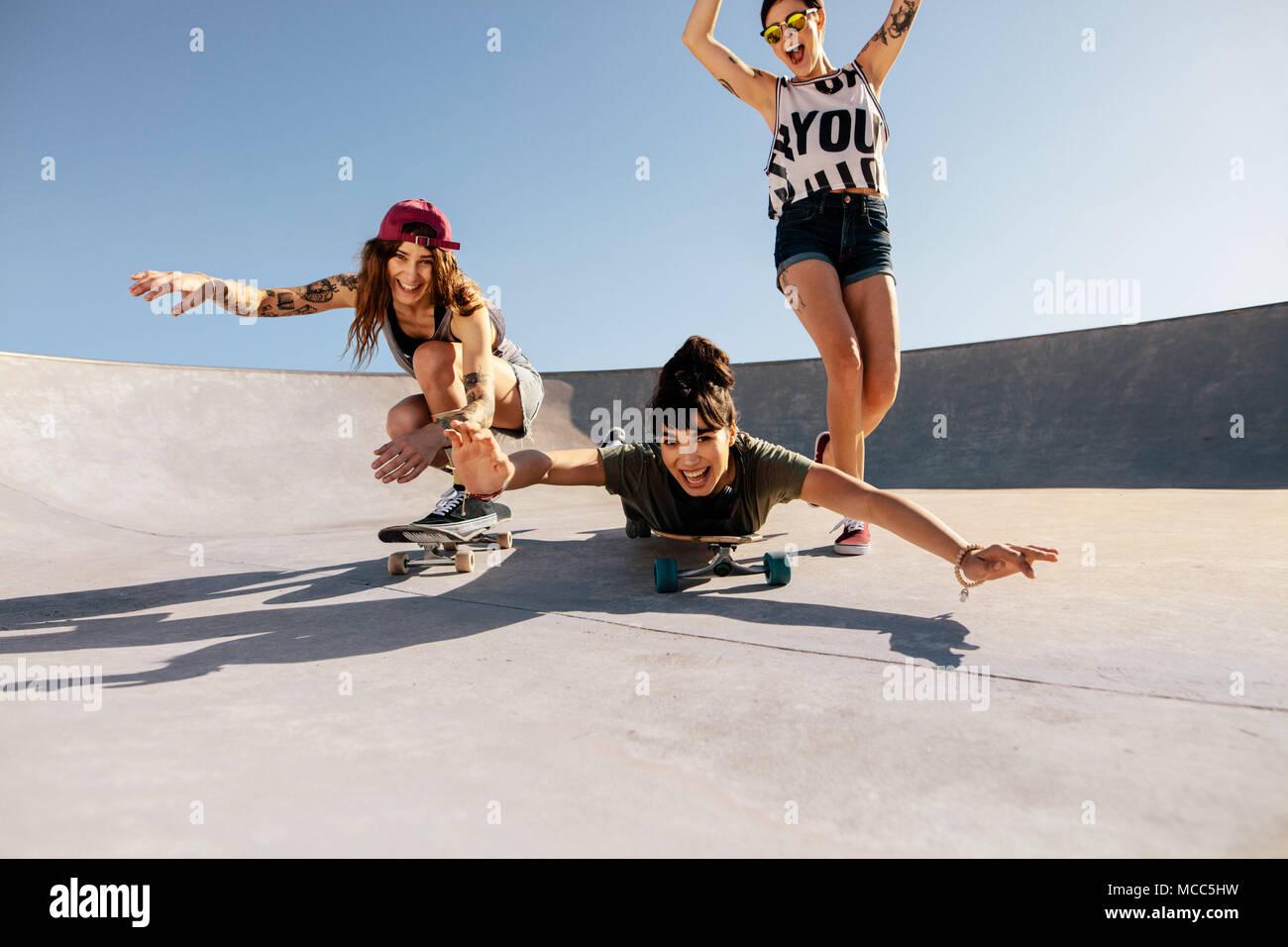 El grupo de niñas montando skateboards y divertirse en el parque de skate. Feliz  mujeres d1e2f633025