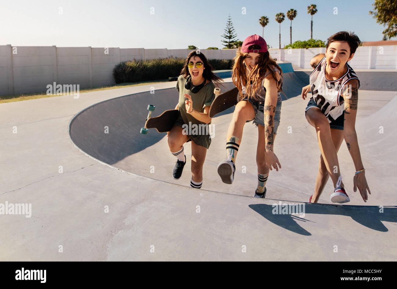 Laughing mujeres subiendo una rampa de skate. El grupo de niñas teniendo un  gran momento d973356536e