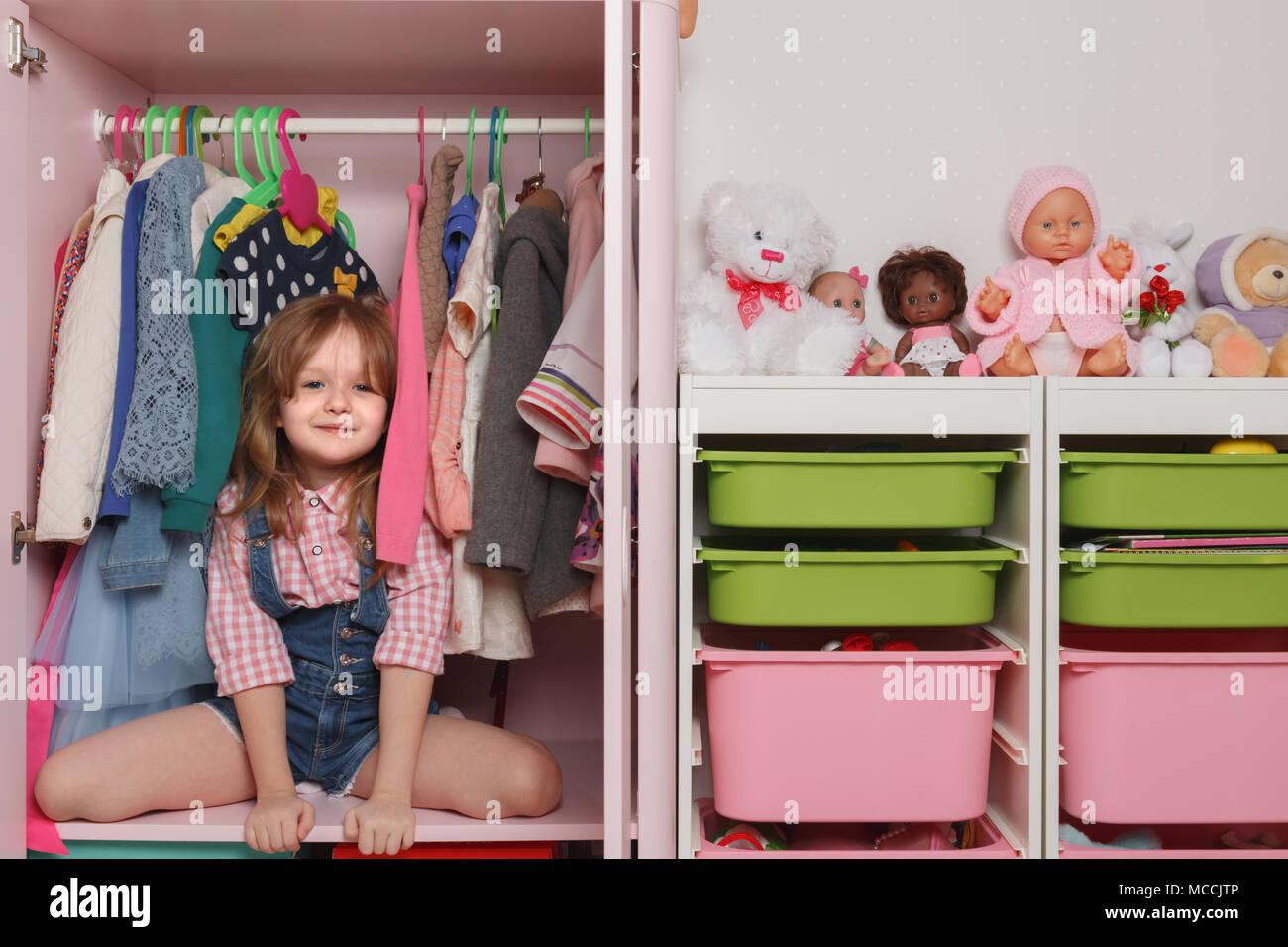 Una niña pequeña está sentada en un armario con un departamento de niños. Sistema de almacenamiento para cosas de niños y juguetes Imagen De Stock