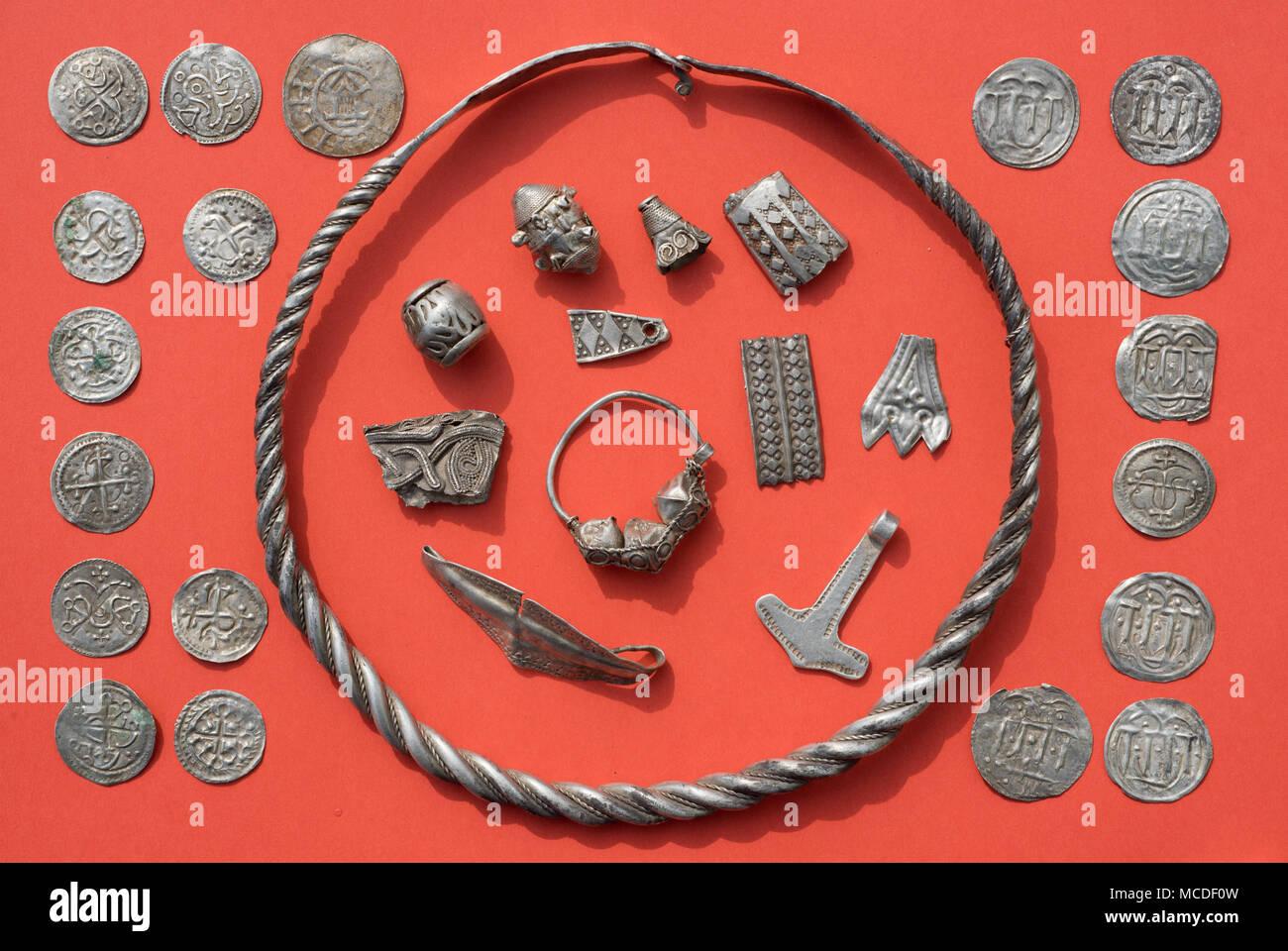 """13 de abril de 2018, Alemania, Schaprode: Algunos de los tesoros de plata Schaprode, incluyendo un anillo espiral de plata, perlas, joyas de plata cut-up, el martillo de Thor, de amuleto y danés y Ottonian monedas en una tabla. Los arqueólogos han descubierto valiosos tesoros de plata escandinavo, predominantemente desde finales del siglo 10, en un campo en la isla alemana de Ruegen. En un área de unos 400 metros cuadrados, cerca del municipio de Schaprode, se recuperaron joyas y alrededor de 500 - 600 monedas, de las cuales más de 100 monedas se remontan al reinado del rey danés Harald """"Bluetooth"""" (910-987). Foto: Stef Foto de stock"""